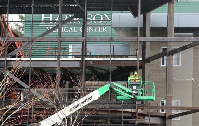 The workforce building a new Harrison hospital in Silverdale is being downsized and construction is being slowed.