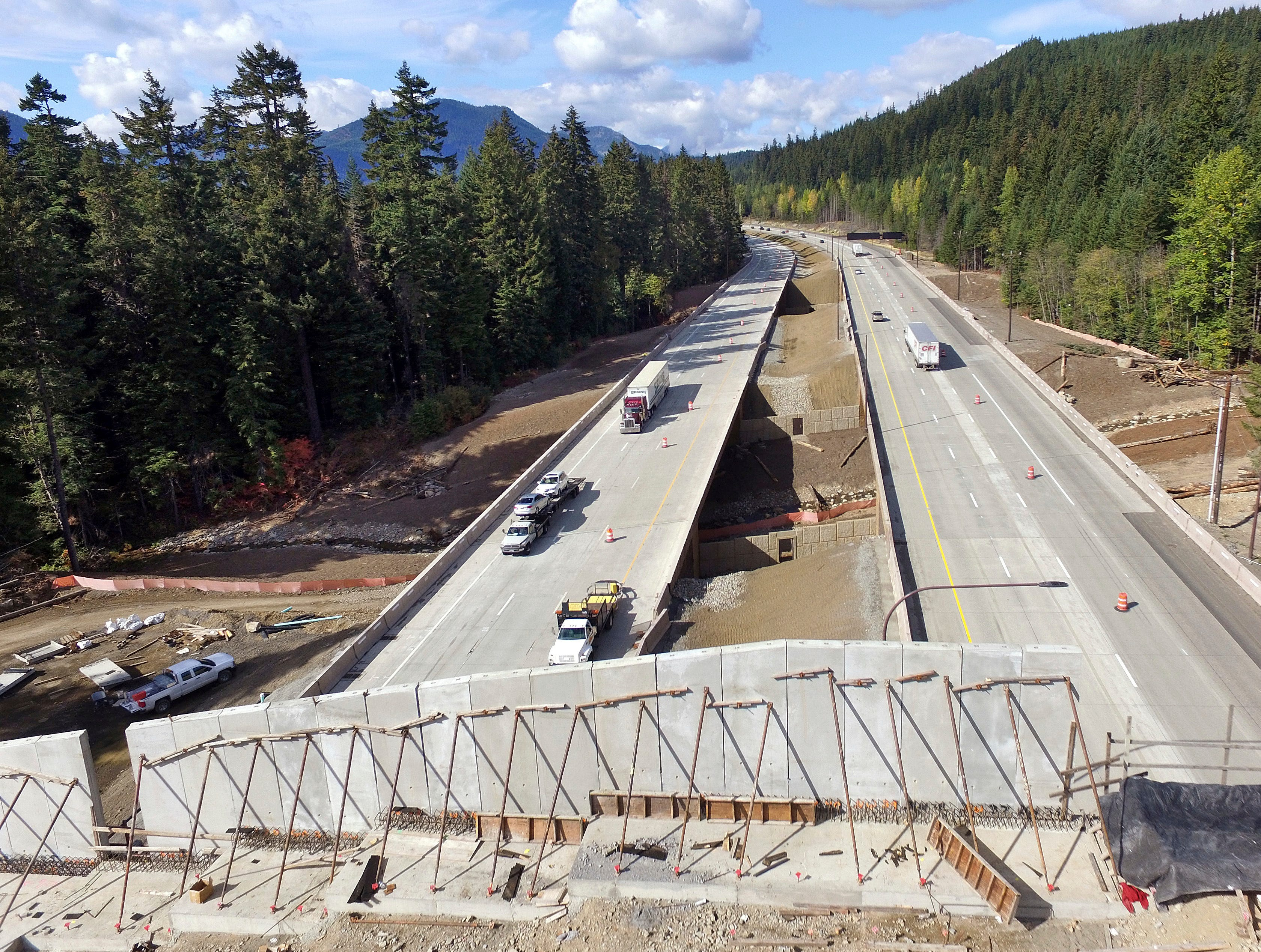 Interstate 90 traffic passes beneath a wildlife bridge under construction on Snoqualmie Pass. The stretch of highway crossing the Cascade Mountains cuts through old growth forest and wetlands, creating a dangerous border for wildlife everything from an elk down to a small salamander. The new crossing gives animals in these mountains a safer option for crossing the road: They'll be able to go above it.