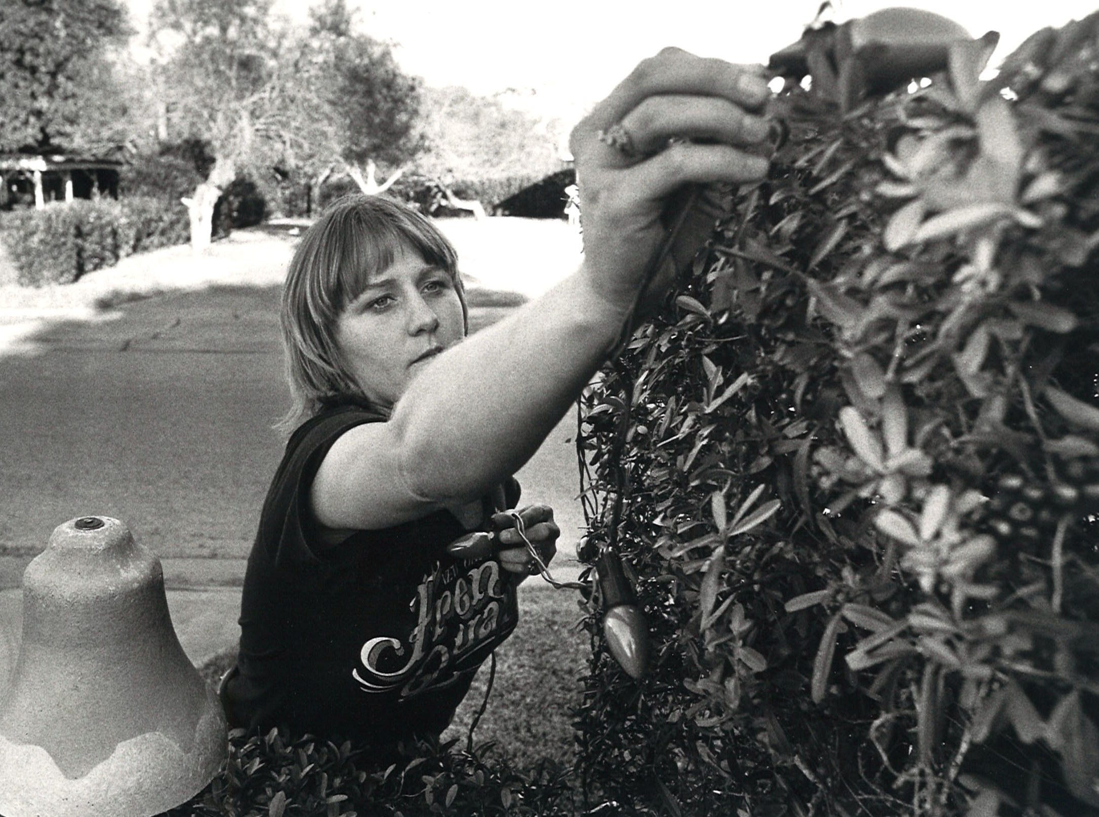 Brenda Aldridge, daughter of Billy Aldridge, works on one of the many different decorations on display at their home on Delaine and Doddridge Dec. 3, 1983. The house was one of the most popular sights during the holiday season for more than 30 years.
