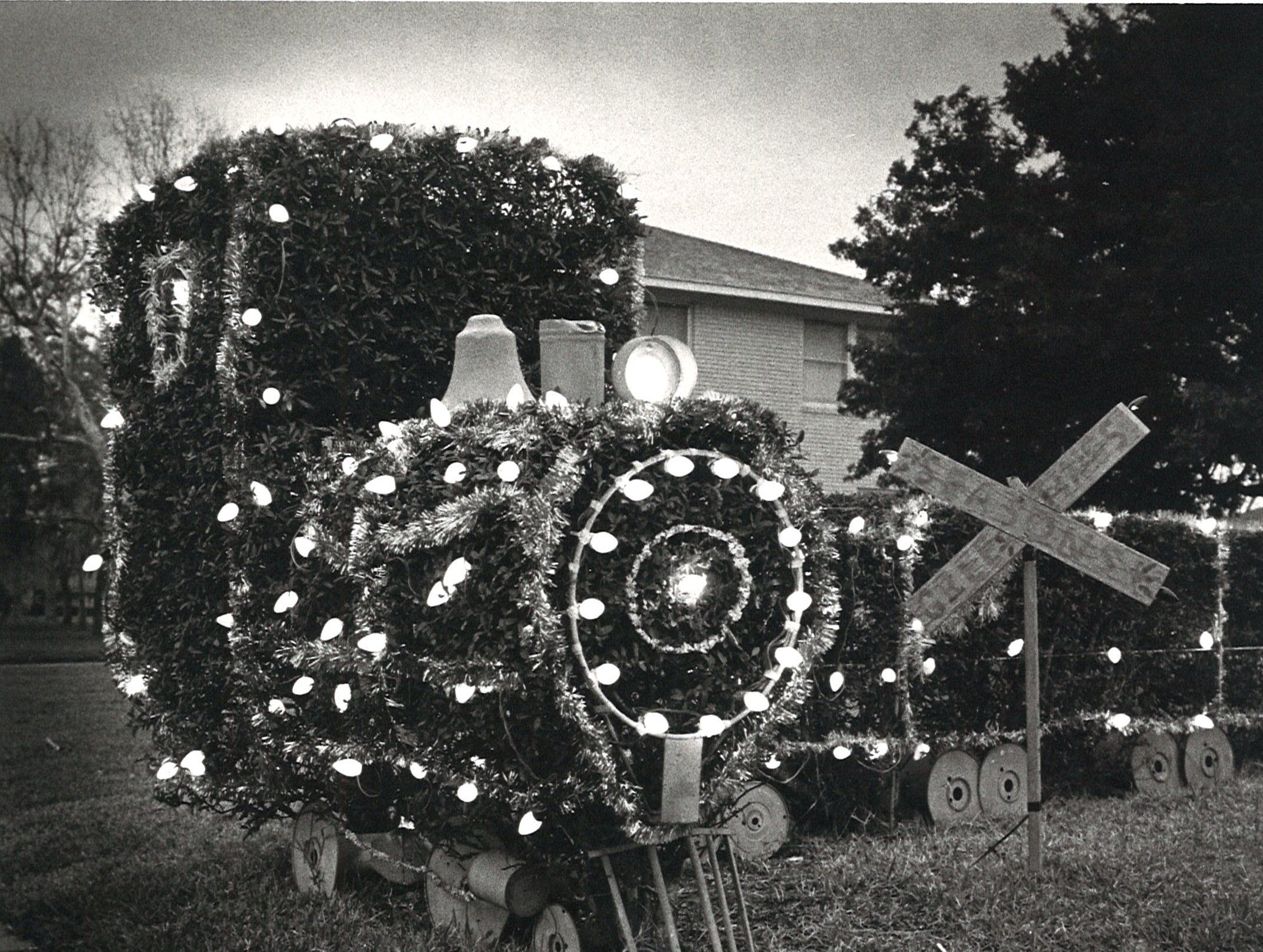 A bush trimmed and decorated into a train shape at the Aldridge home on Delaine and Doddridge in 1980. Bill Aldridge decorated his home with many purchased and handmade decorations for more than 30 years.