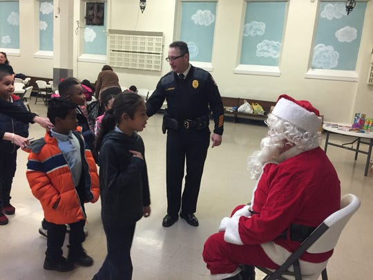 Delaware River Port Authority Police Officer John Santiago (center) plays Santa's helper at Holy Name School in North Camden Wednesday. Santiago went to the school in the 1970s.