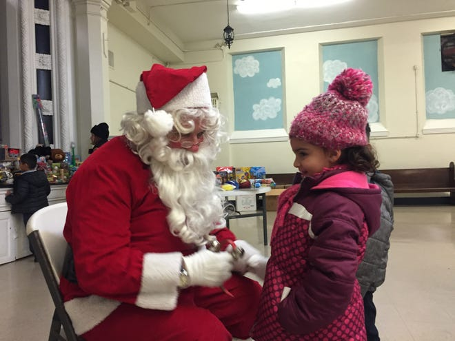 Santa Claus (aka Bruce Shannon) talks to Nelania Hidalgo, a kindergartner at Holy Name School in North Camden. We're pretty sure she made the 'Nice' list.