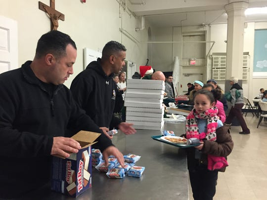 Delaware River Port Authority Police officers Nick Deluca (left) and Jose Espino hand out ice cream sandwiches to students at Holy Name School in North Camden Wednesday.