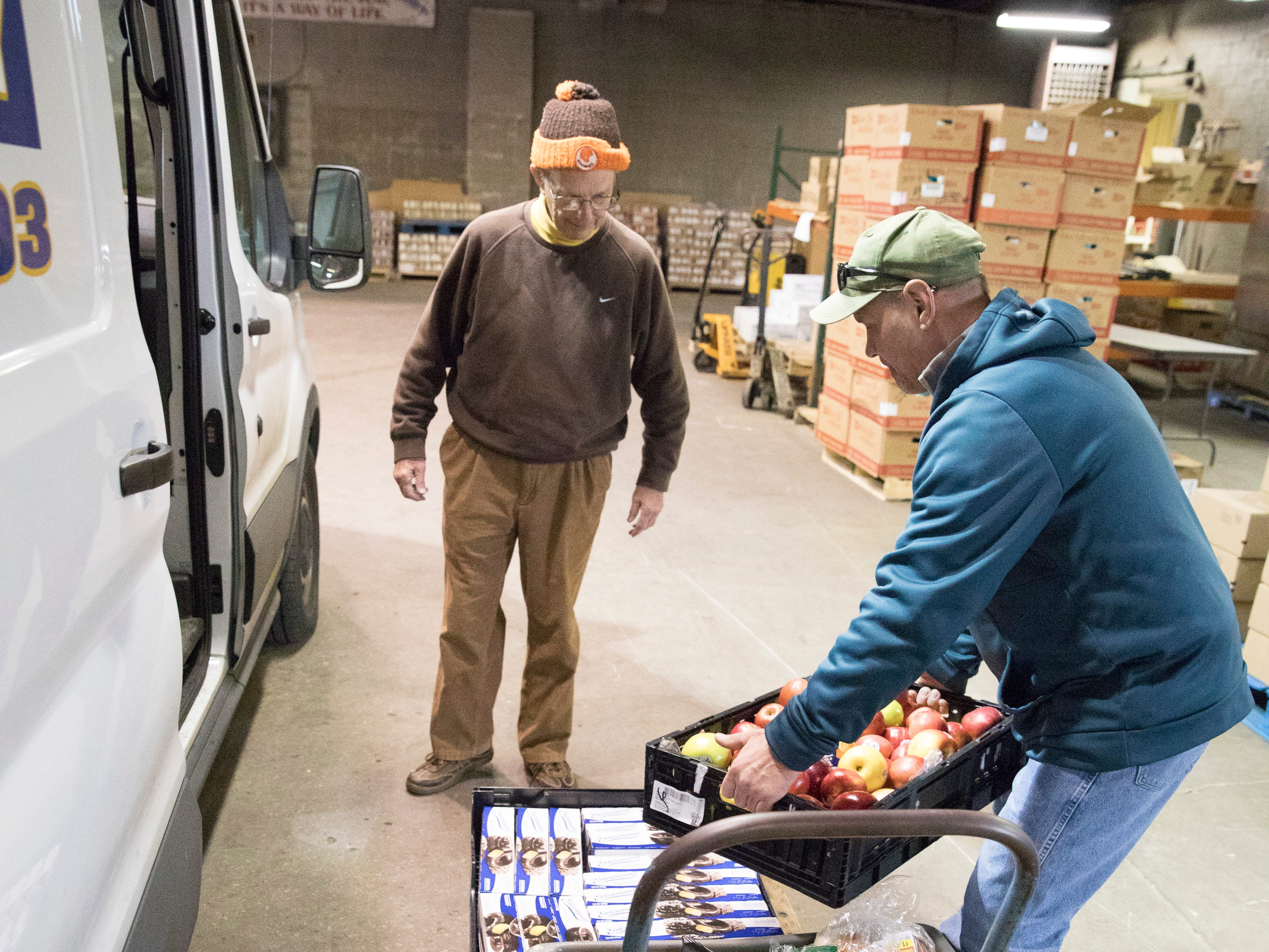 Volunteer Nate Lovett and Alvis House volunteer Steve Durham unload a truck of donated food at the Good Samaritan Food Pantry on December 10, 2018.