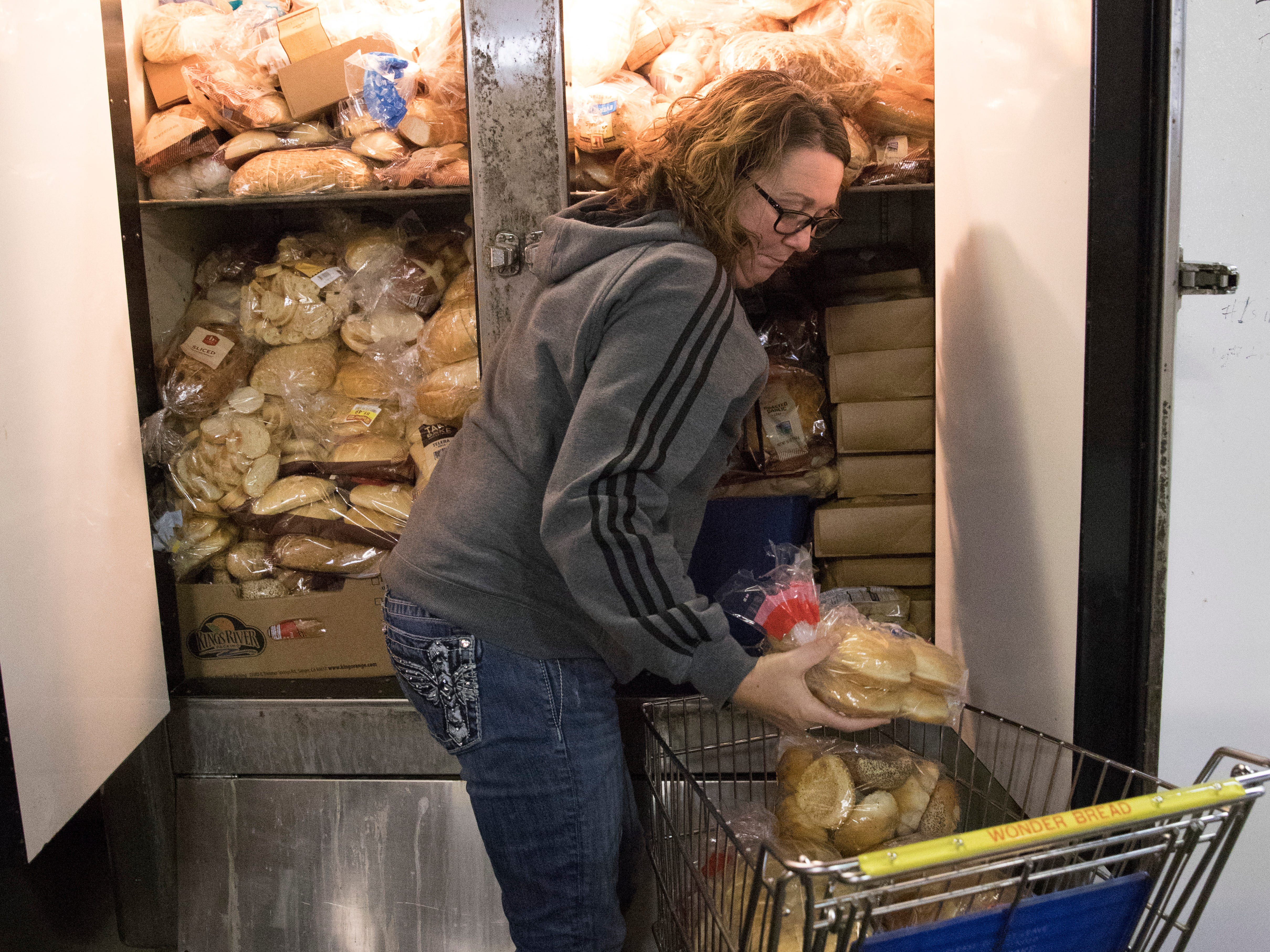 Missy Johnson gets bread from the stocked fridge in the Good Samaritan Food Pantry warehouse. Bread is one of its most popular items and is received from Kroger, one of its many partners.
