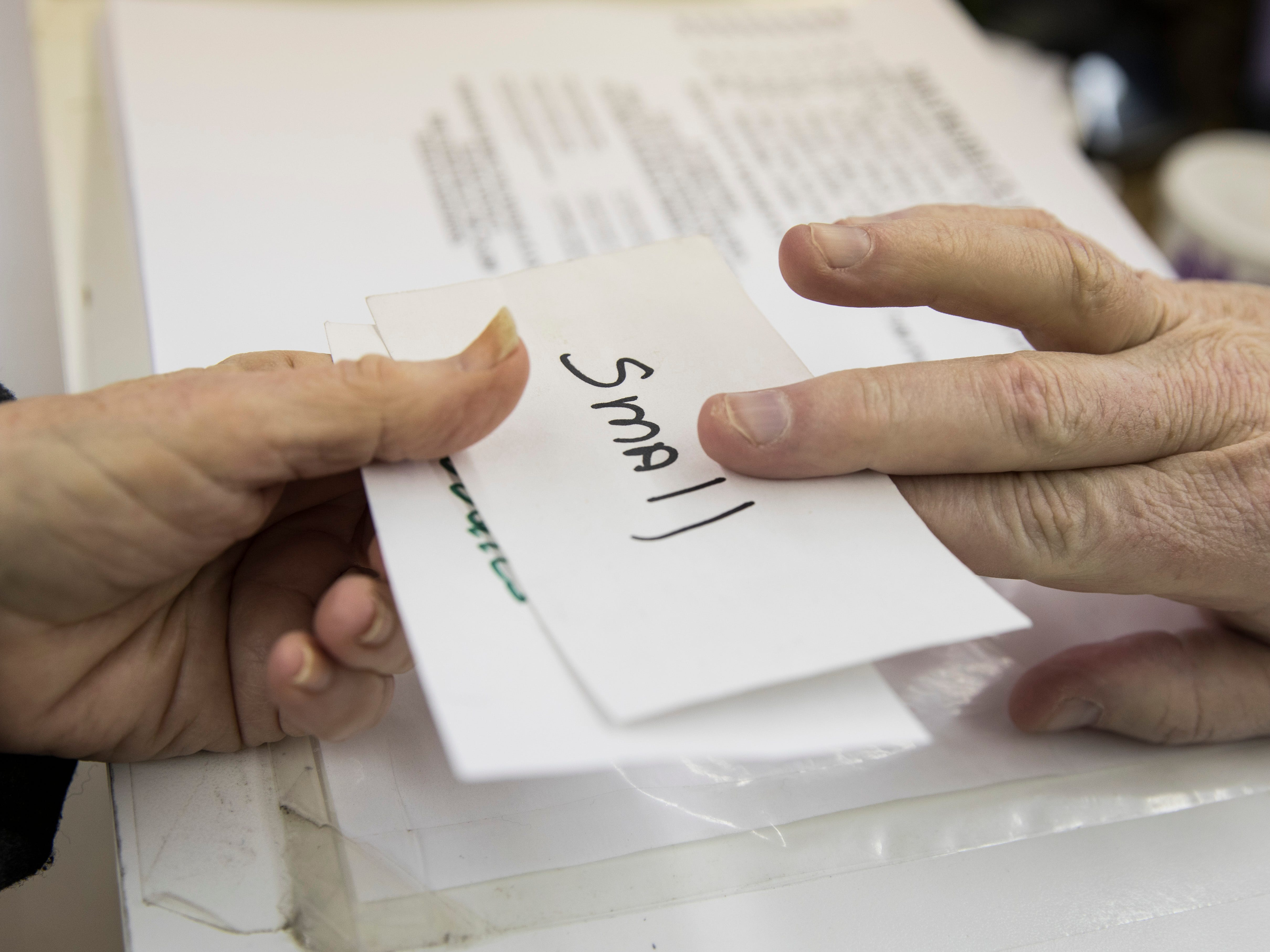 """Good Samaritan Food Pantry clients receive cards that may be labeled """"small"""" to stand for the household size they are getting groceries for. Different local agencies also give referral slips to clients to help them with their needs."""