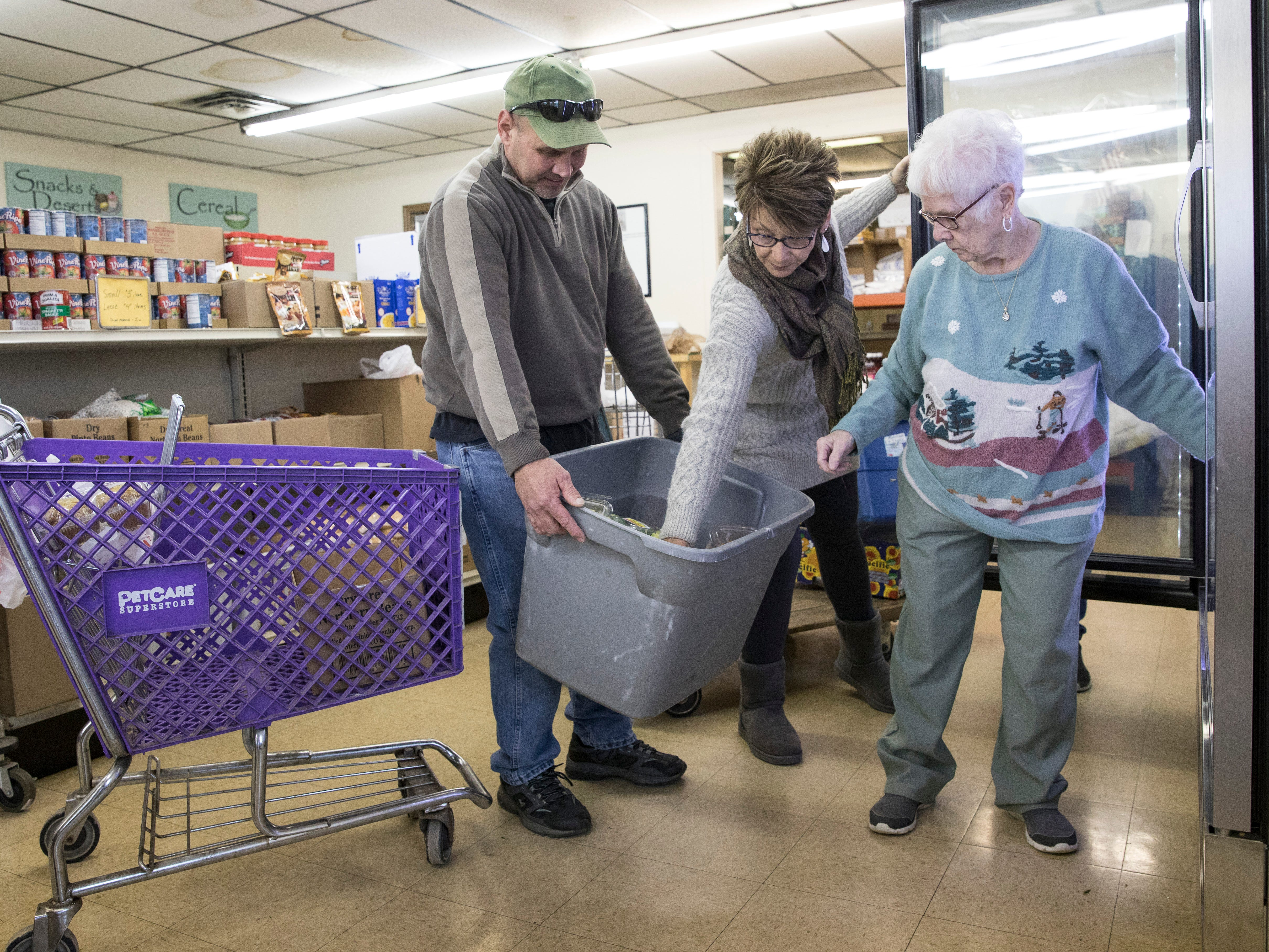 """Steve Durham holds a container full of fruit as Denise Litter and Carolyn Russell stock the coolers at the Good Samaritan Food Pantry. """"Items like fruit are popular and don't last long,"""" said Russell."""