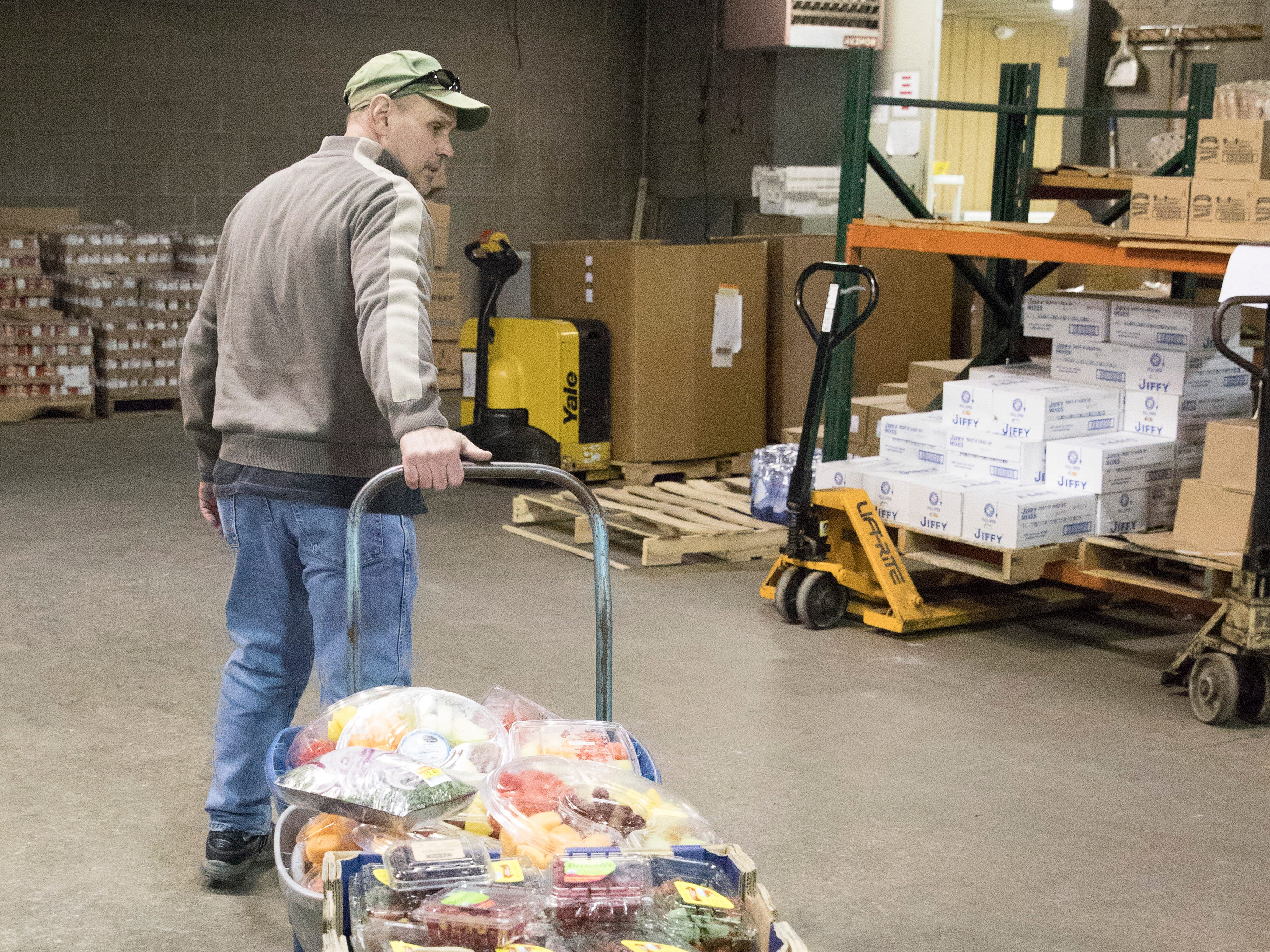 Alvis House volunteer Steve Durham wheels a load of fruit through the Good Samaritan Food Pantry warehouse to be placed on the shelves of the pantry store Monday morning in Chillicothe, Ohio.