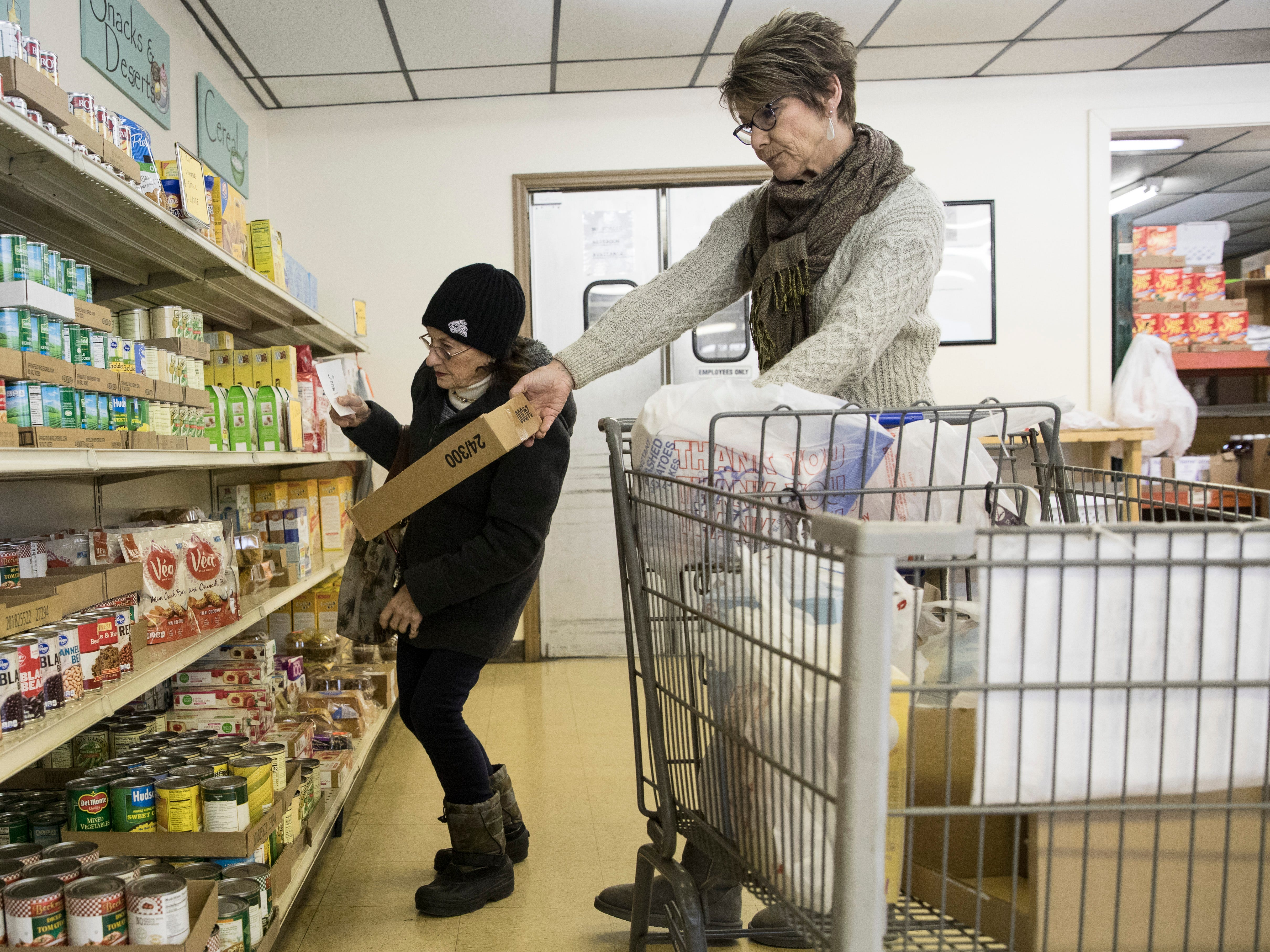 """Chillicothe native Edie Adkins, left, gets help shopping from Good Samaritan Food Pantry volunteer Denise Litter, a volunteer at the pantry for over four years on December 10, 2018, in Chillicothe, Ohio. """"I like coming here,"""" said Adkins. """"It's very helpful and lets me keep more money to spend on my bills."""""""