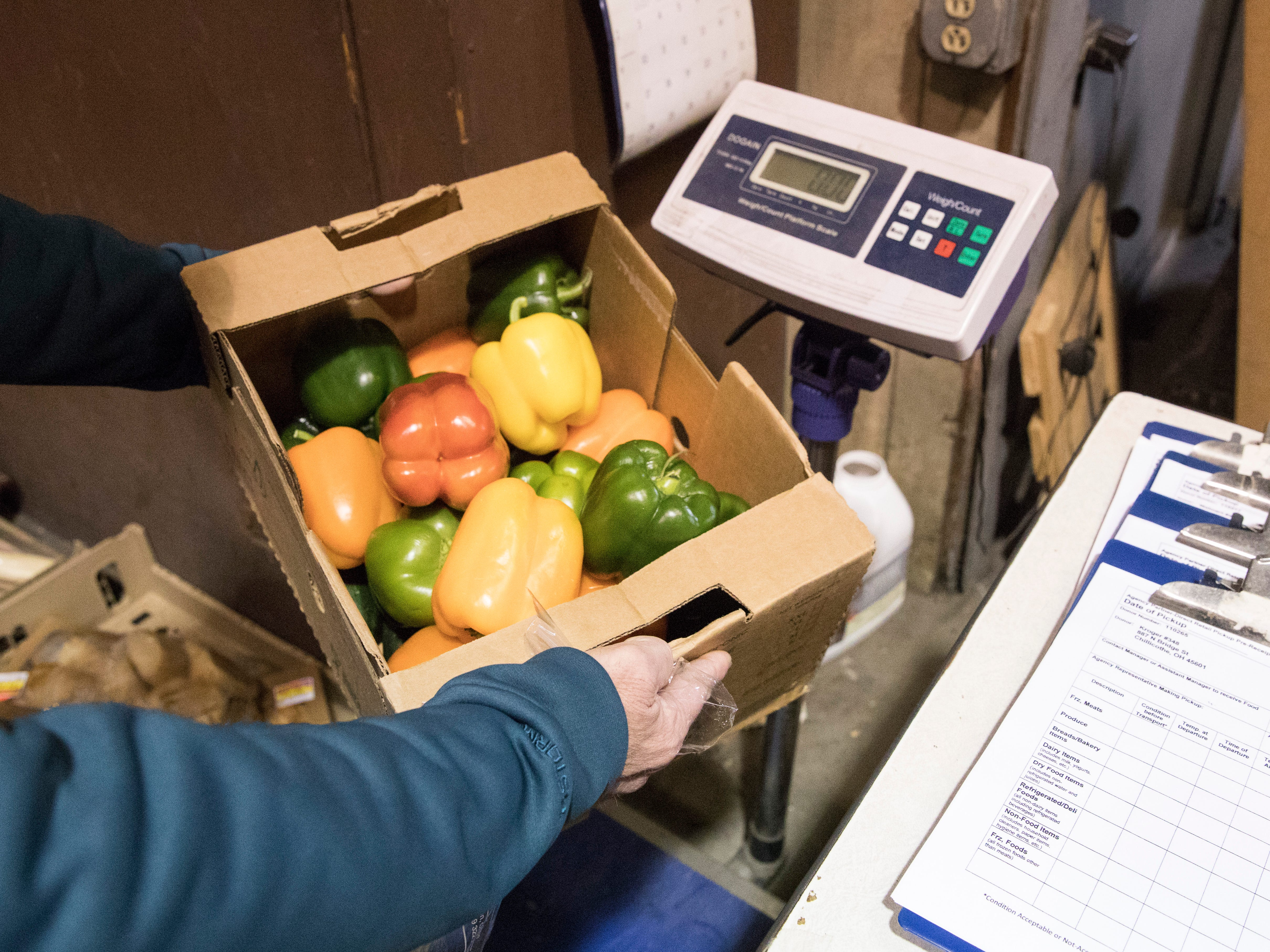 """A box of peppers is weighed by Steve Durham and Mike Thomson before it is put out for its various clients. """"We have to weigh the food because our board of trustees likes to know how many pounds of food come through the pantry,"""" said operations manager Mike Thompson."""