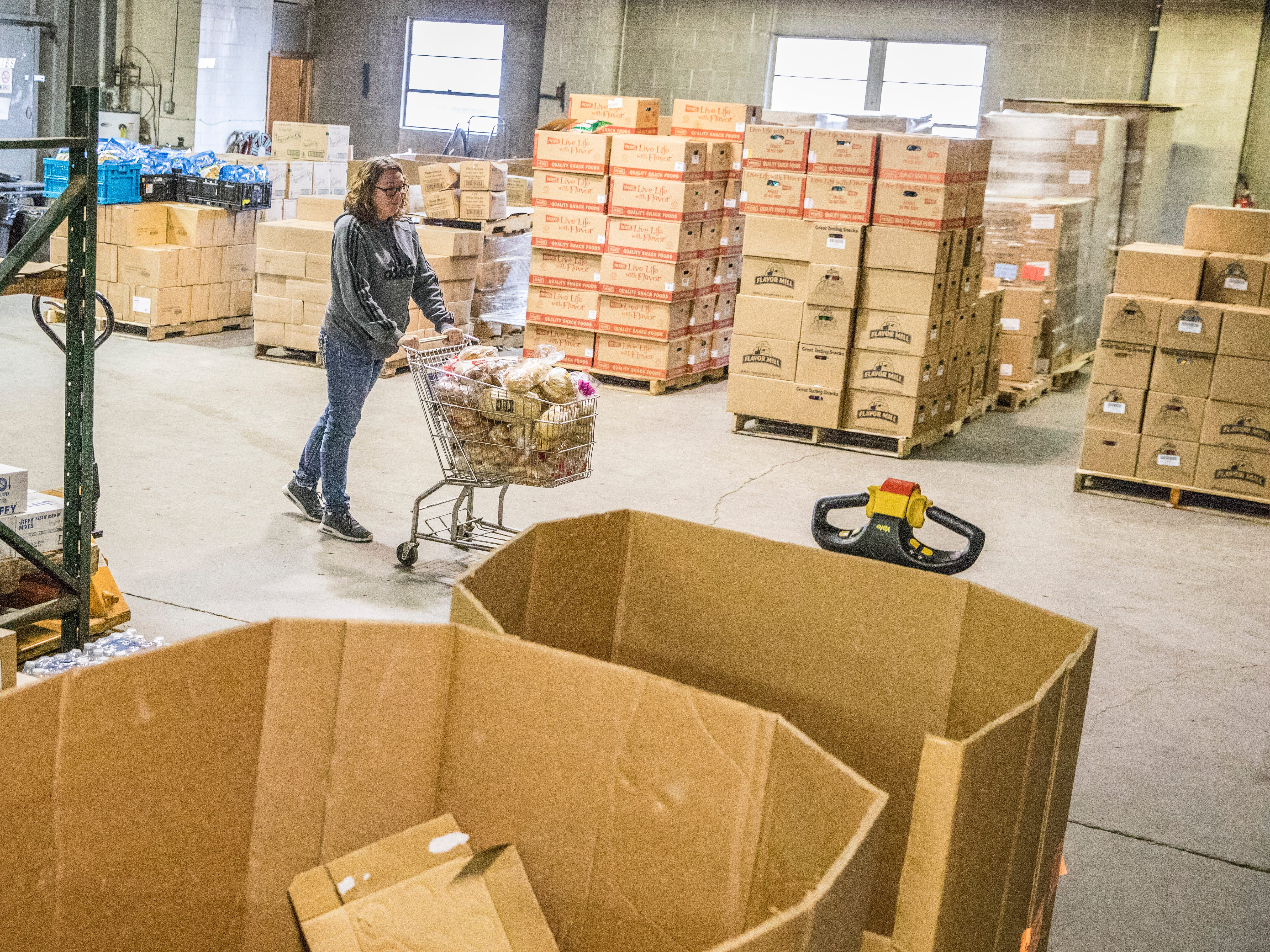 Missy Johnson wheels a grocery cart full of bread through the warehouse of the Good Samaritan Food Pantry for it to be stocked for clients.