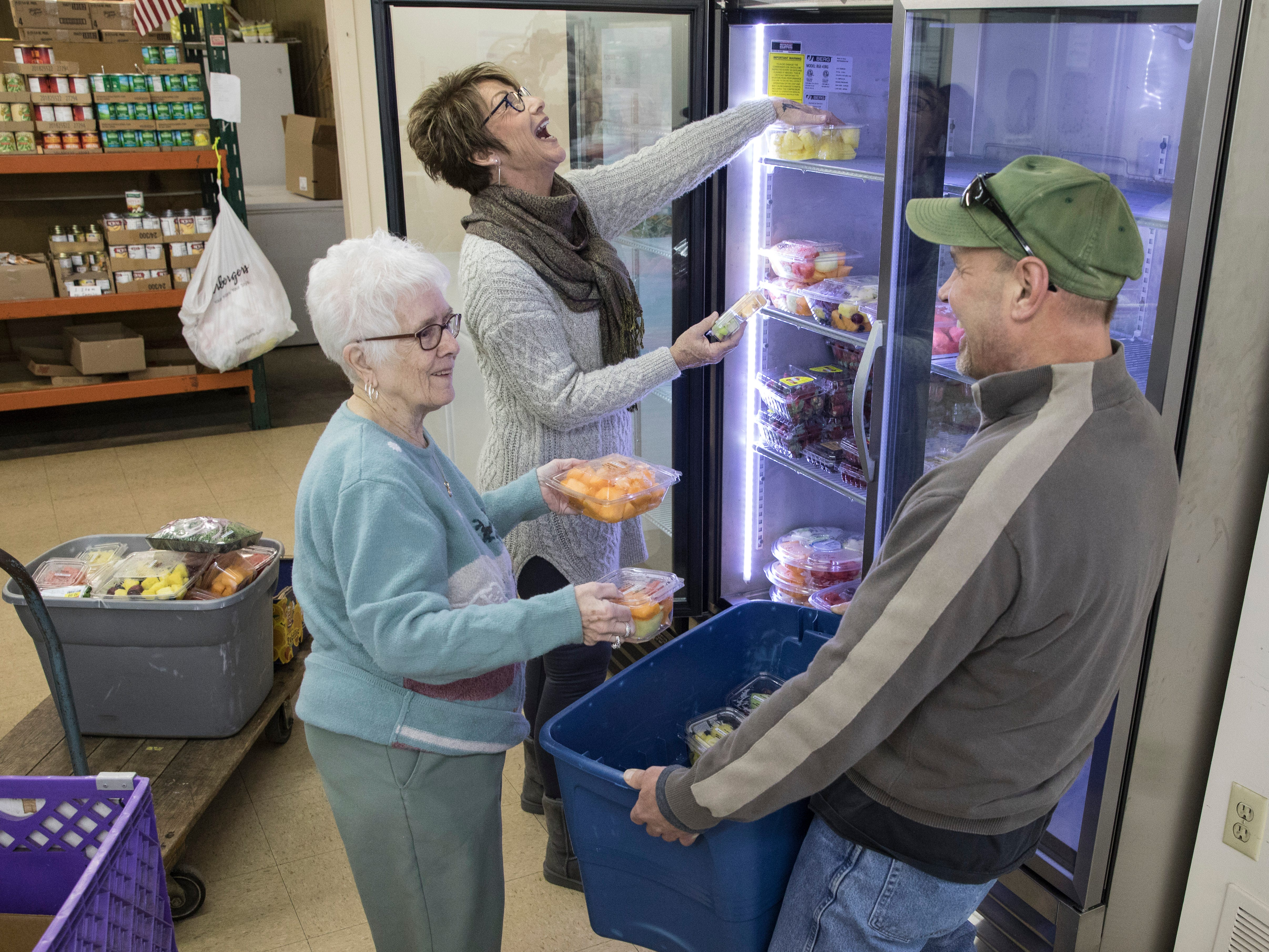 (L-R) Carolyn Russell, Denise Litter, and Steve Durham laugh as they stock fruit and try hard to remember how long they have volunteered at the Good Samaritan Food Pantry and how they enjoy helping others.