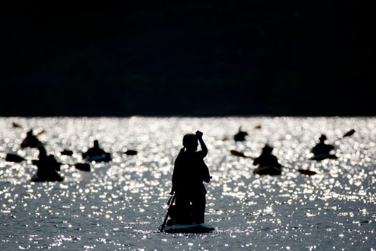 Darion Ziegler paddle boards down the Ohio River during the 17th annual Ohio River Paddlefest in Cincinnati on Saturday, Aug. 4, 2018.