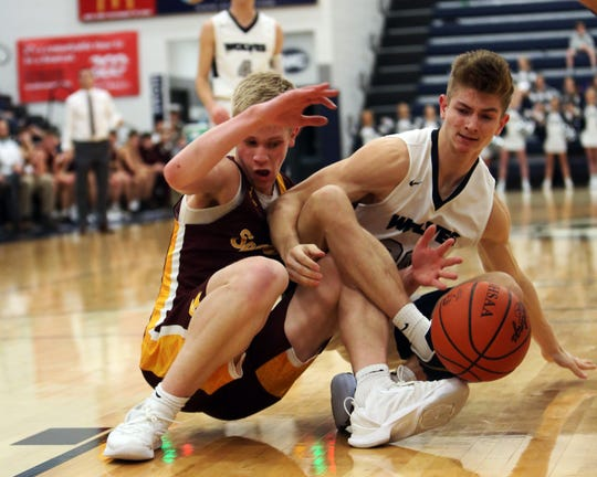 West Clermont center Jackson Ames (right) and Turpin forward Trey Shetler battle for a loose ball. Turpin defeated West Clermont, 70-51.