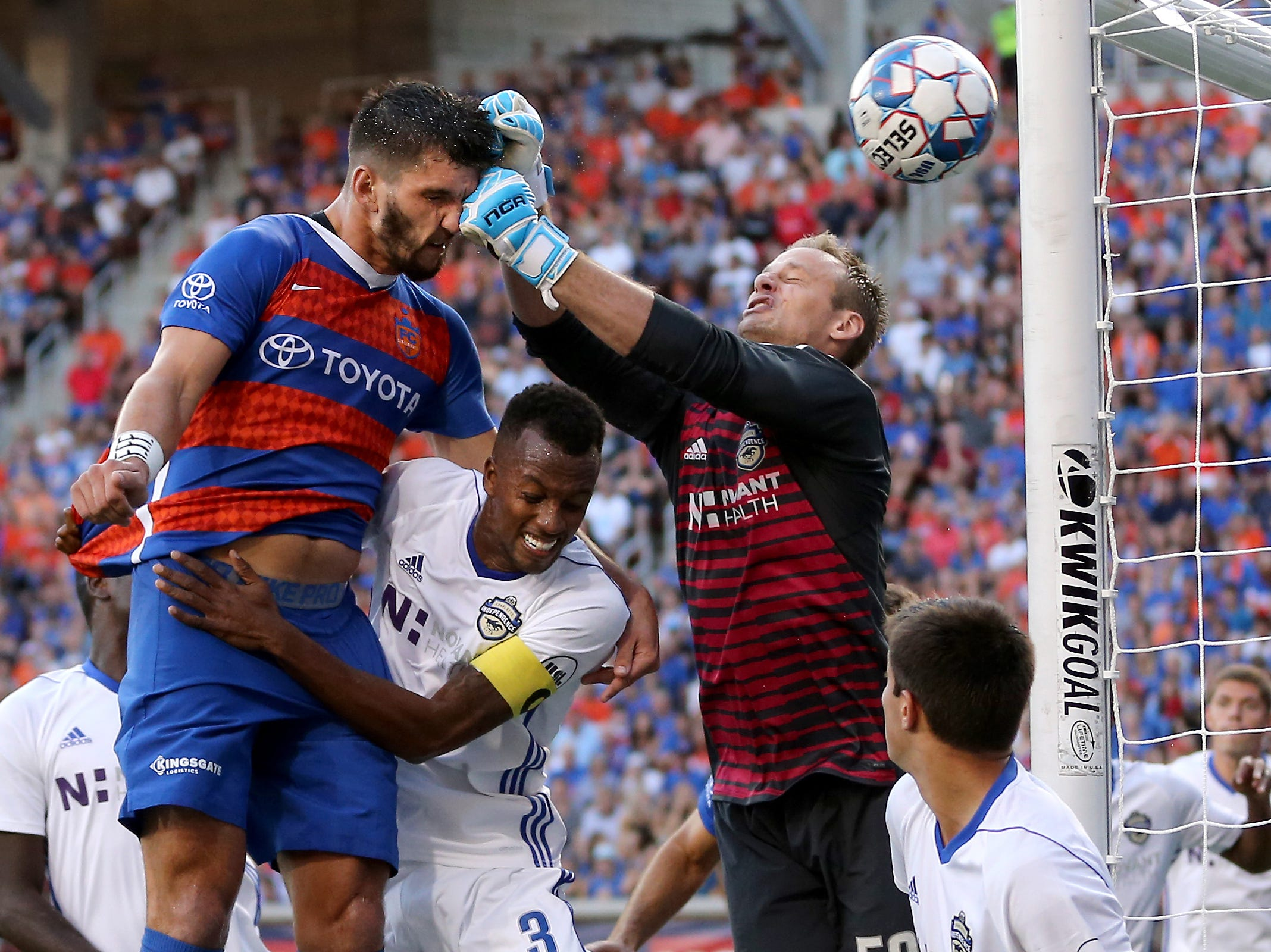 I mainly cover Cincinnati-area sports. Sports action photos are common, but unique images that capture peak action and difficulty of competition are difficult to capture and anticipate. In this frame, FC Cincinnati defender Forrest Lasso is punched in the face by Charlotte Independence goalkeeper Andrew Dykstra (50) on an attempt on goal during a game, Wednesday, July 18, 2018, at Nippert Stadium.