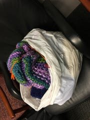 This bag of hats with scarves tucked inside them was distributed to one of the United Way chapters on Tuesday.