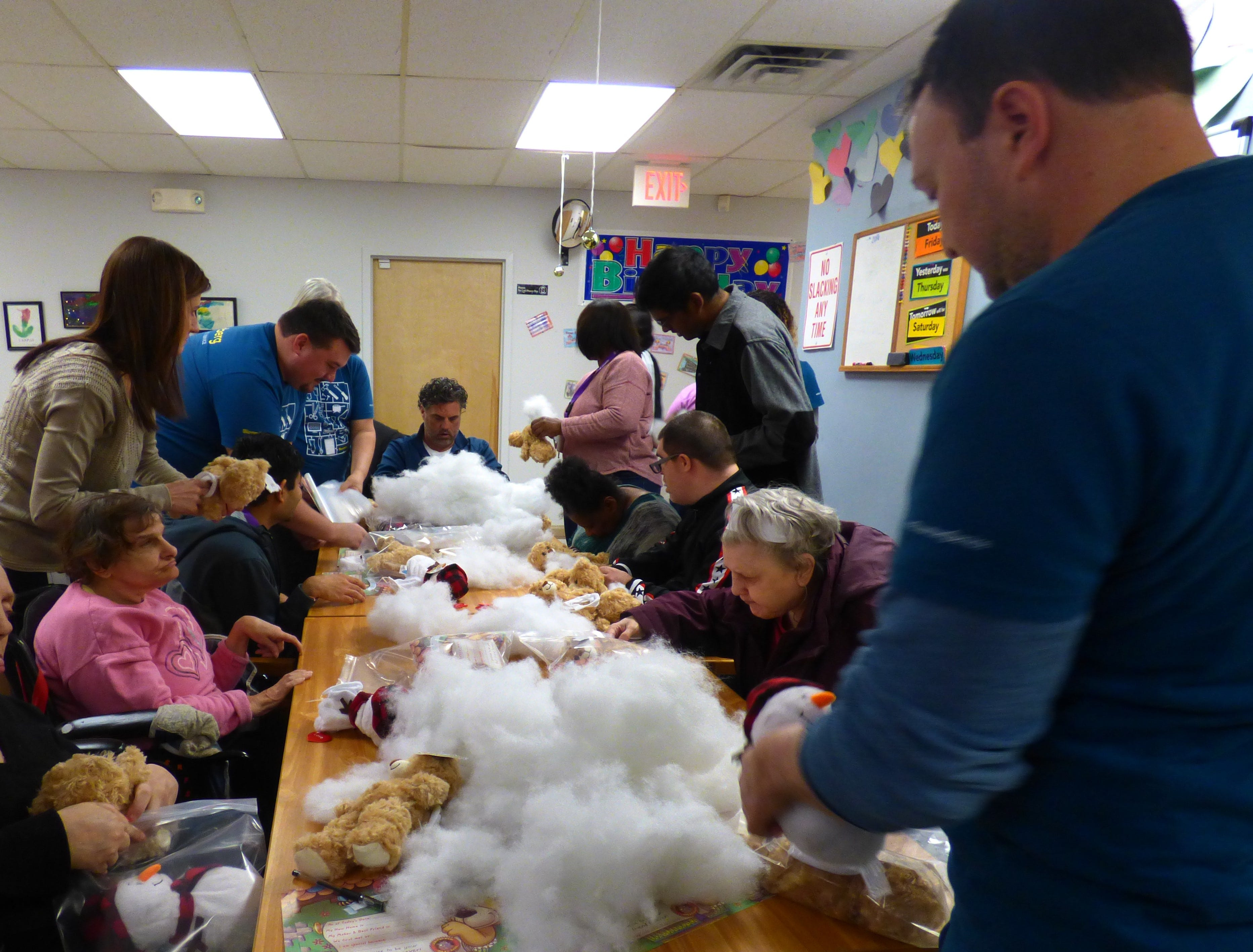 Consumers in Enable's Princeton day program and volunteers from Bloomberg are working on making Build-a-Bears. One bear for the consumer to take home and one to donate to The Children's Home Society.