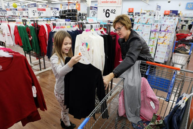 Jenna Wharton, 7, and volunteer Melody Lowe look at an outfit at Walmart in Coshocton during the Christmas Castle event on Tuesday.