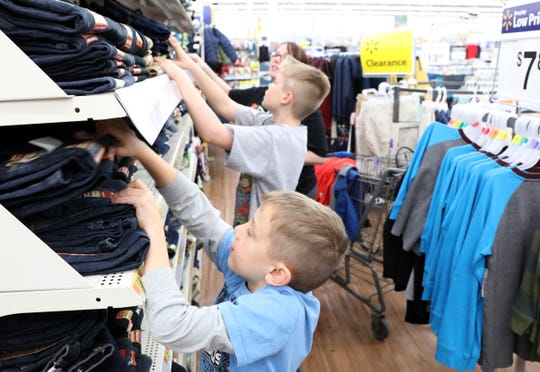 Christian Hogue, 9, and his brother David, 11, shop with volunteer Nicole Alloway at Walmart in Coshocton during the Christmas Castle event on Tuesday.