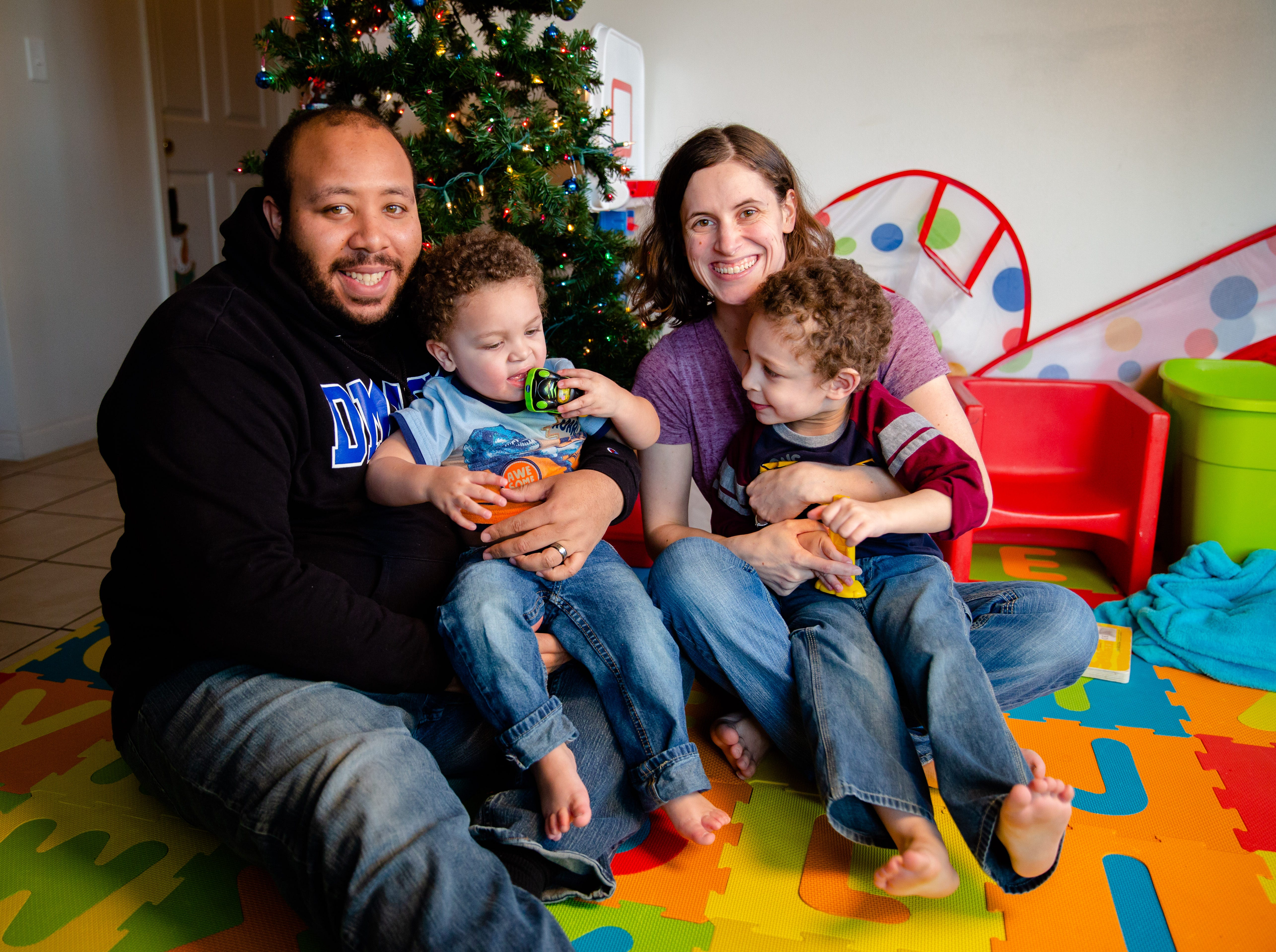 Maurice McFalls holds his son Oliver, 2, as his wife Andrea  holds their son Benjamin, 3, at their Des Moines apartment Tuesday, Dec. 11, 2018.