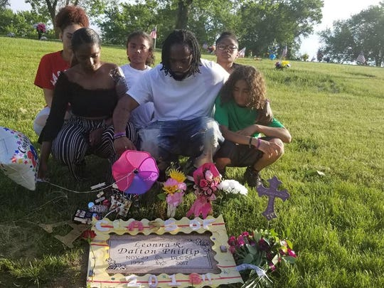 Claude Phillip, of Des Moines, with family members at the grave of his daughter, Leonna Dalton-Phillip, in Omaha.
