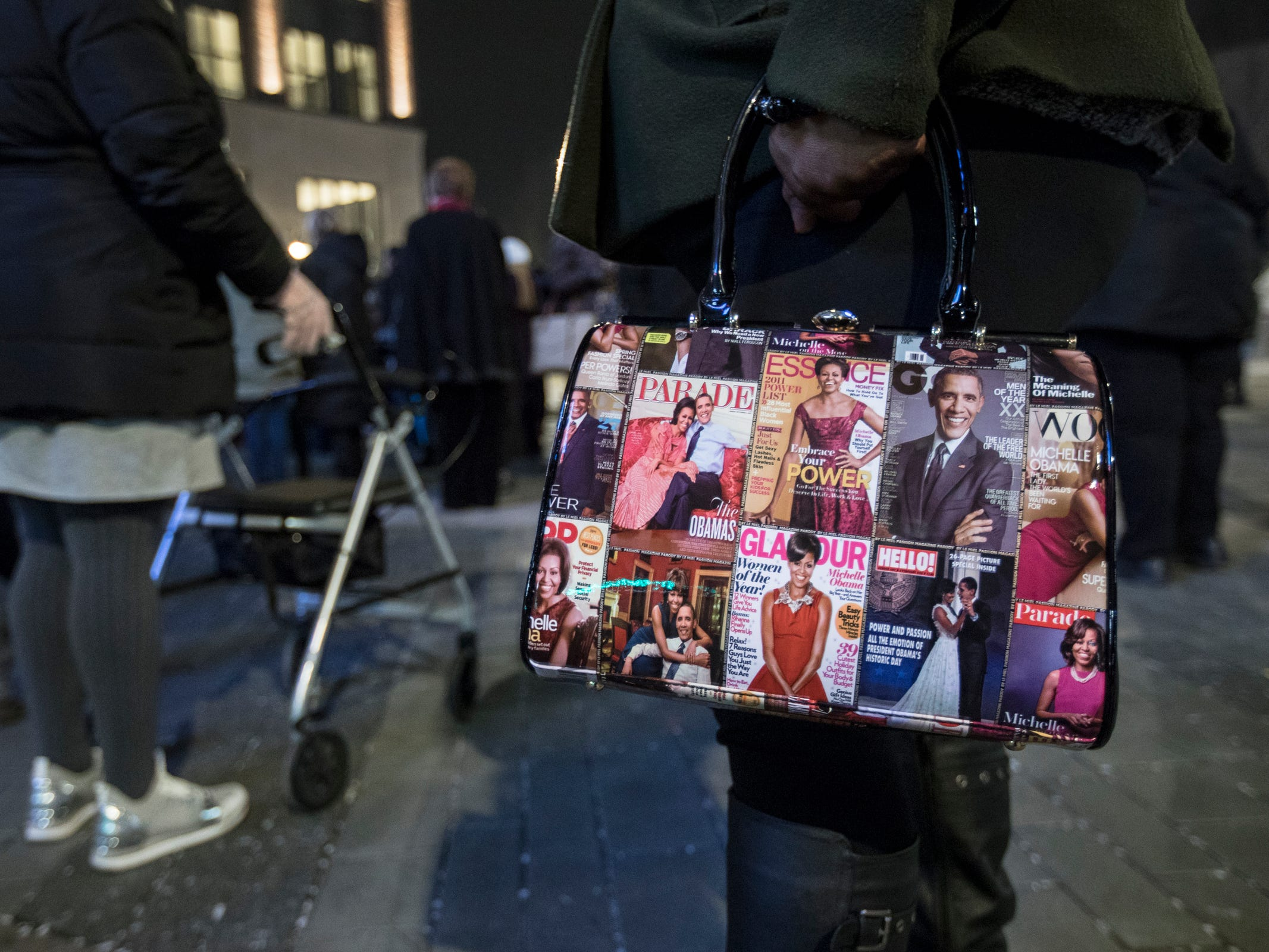"Devin Massengale of Detroit stands in the line with her Obama handbag as she waits to see Michelle Obama's ""Becoming"" book tour at the Little Caesars Arena in Detroit, Tuesday, Dec. 11, 2018."