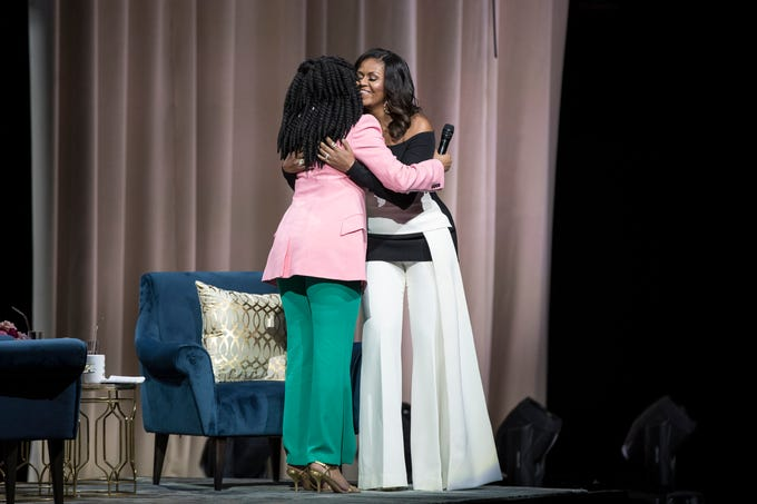 "Michelle Obama hugs comedian Phoebe Robinson as she walk on stage during her ""Becoming"" book tour at the Little Caesars Arena in Detroit, Tuesday, Dec. 11, 2018."