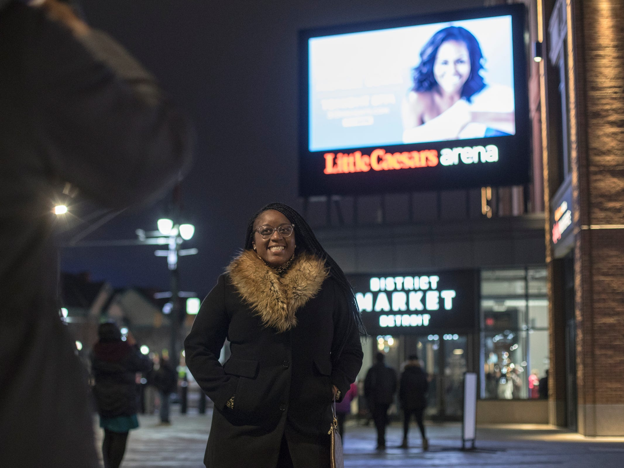 "Nina Davis of Macomb, left, takes a photo of her friend DJ Cherif of Ann Arbor before Michelle Obama's ""Becoming"" book tour at the Little Caesars Arena in Detroit, Tuesday, Dec. 11, 2018."