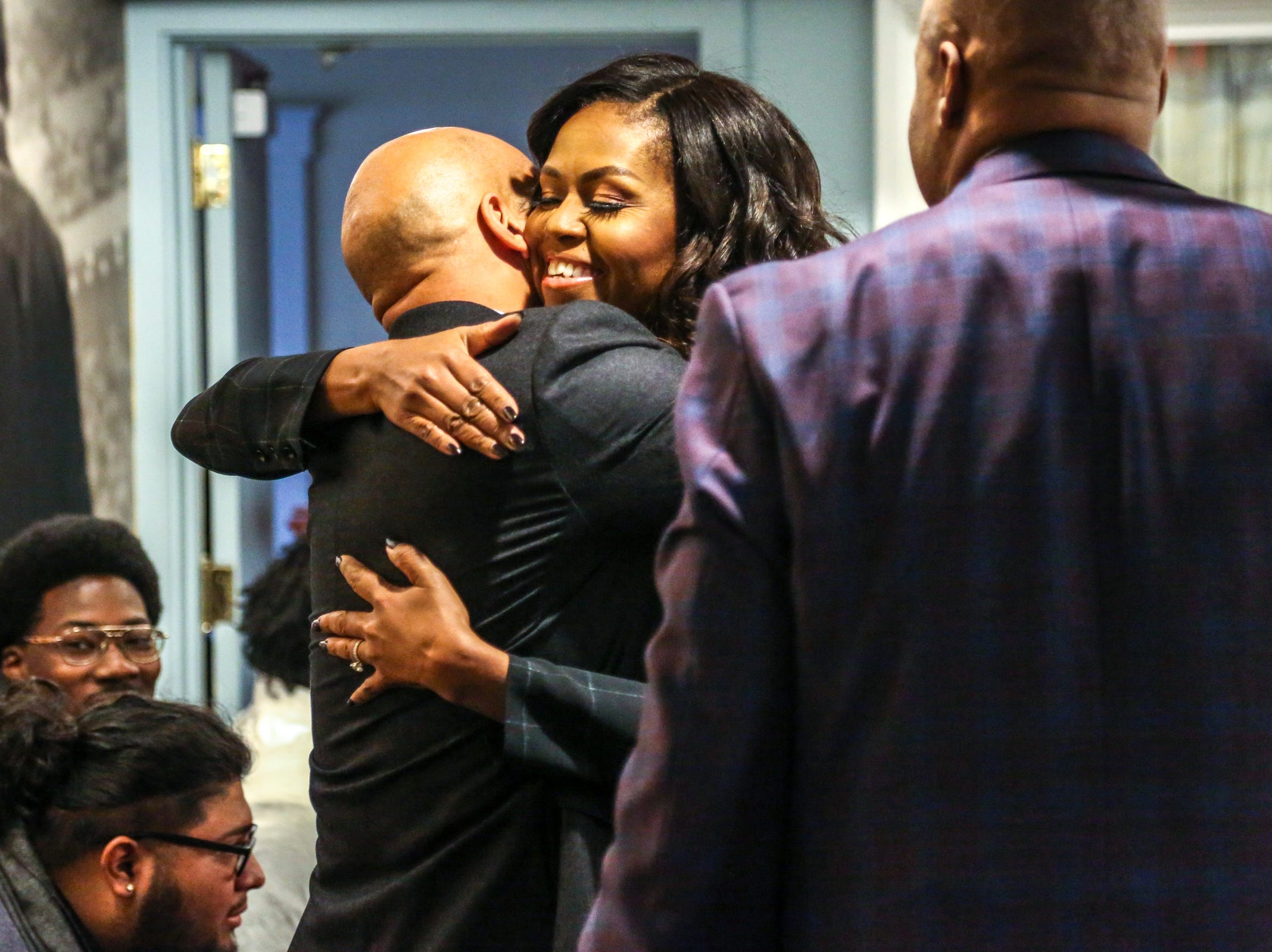 Former First Lady Michelle Obama greets Keegan-Michael Key during a roundtable with young black men from Wayne State University alongside her brother Craig Robinson, right, at Motown Museum in Detroit on Tuesday, Dec. 11, 2018.