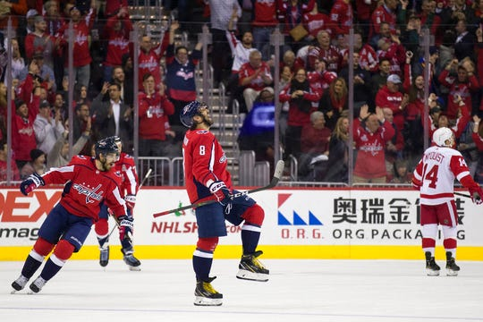 Washington Capitals left wing Alex Ovechkin (8), from Russia, celebrates his goal with defenseman Michal Kempny, from the Czech Republic, at left, in the first period of an NHL hockey game against the Detroit Red Wings, , Tuesday, Dec. 11, 2018, in Washington.