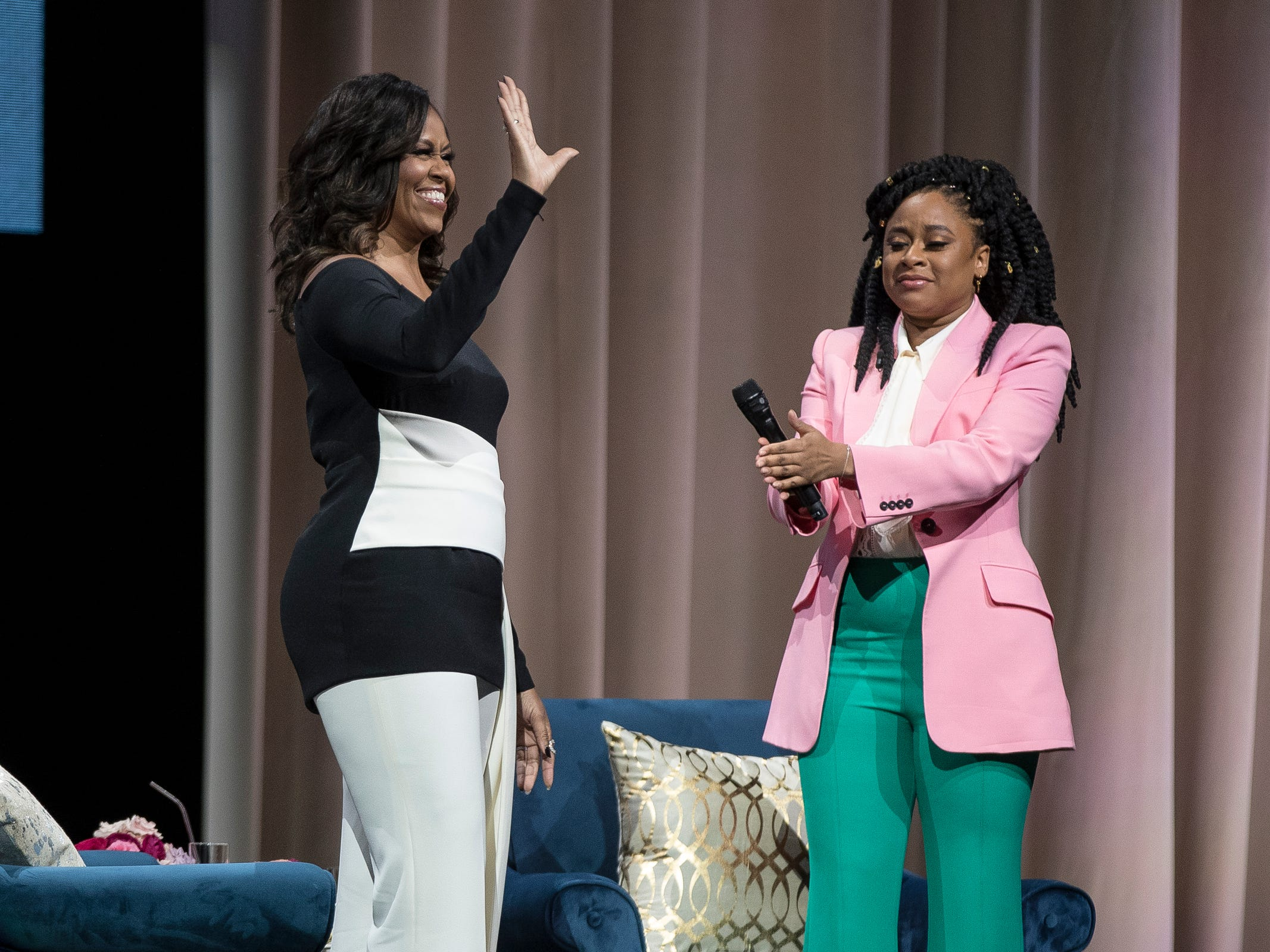 "Michelle Obama waves at the crowd as she walk on stage during her ""Becoming"" book tour at the Little Caesars Arena in Detroit, Tuesday, Dec. 11, 2018. Next to her is comedian Phoebe Robinson."
