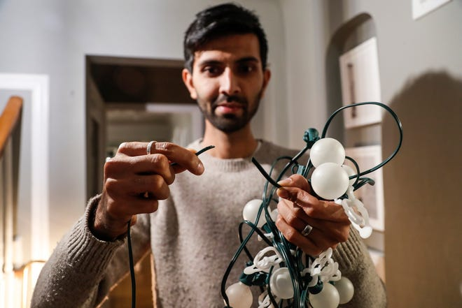Perry Shah of Pleasant Ridge shows the broken lighting wire at his home. He believes squirrels are the culprits.
