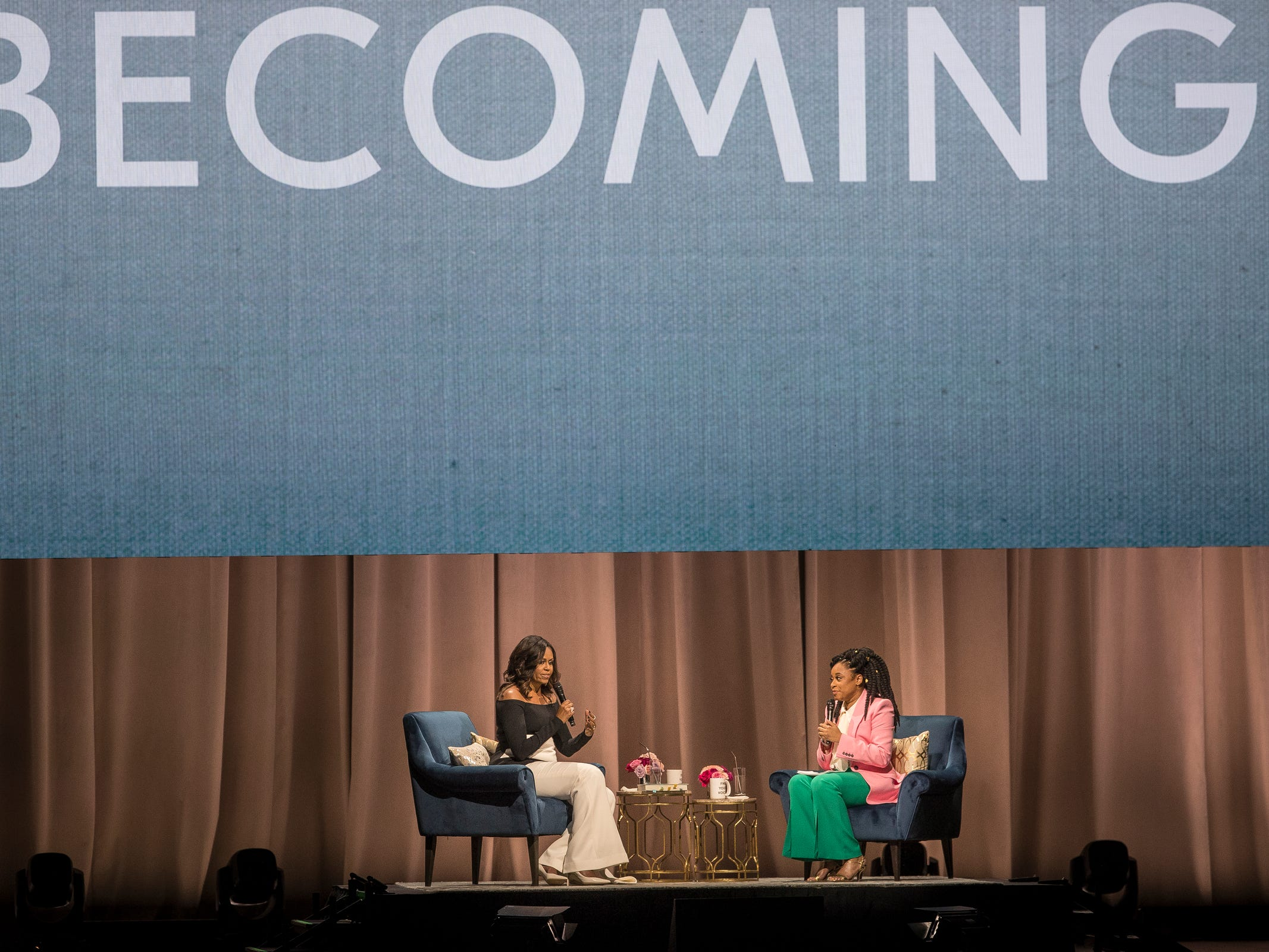 "Michelle Obama, left, talks to comedian Phoebe Robinson during her ""Becoming"" book tour at the Little Caesars Arena in Detroit, Tuesday, Dec. 11, 2018."