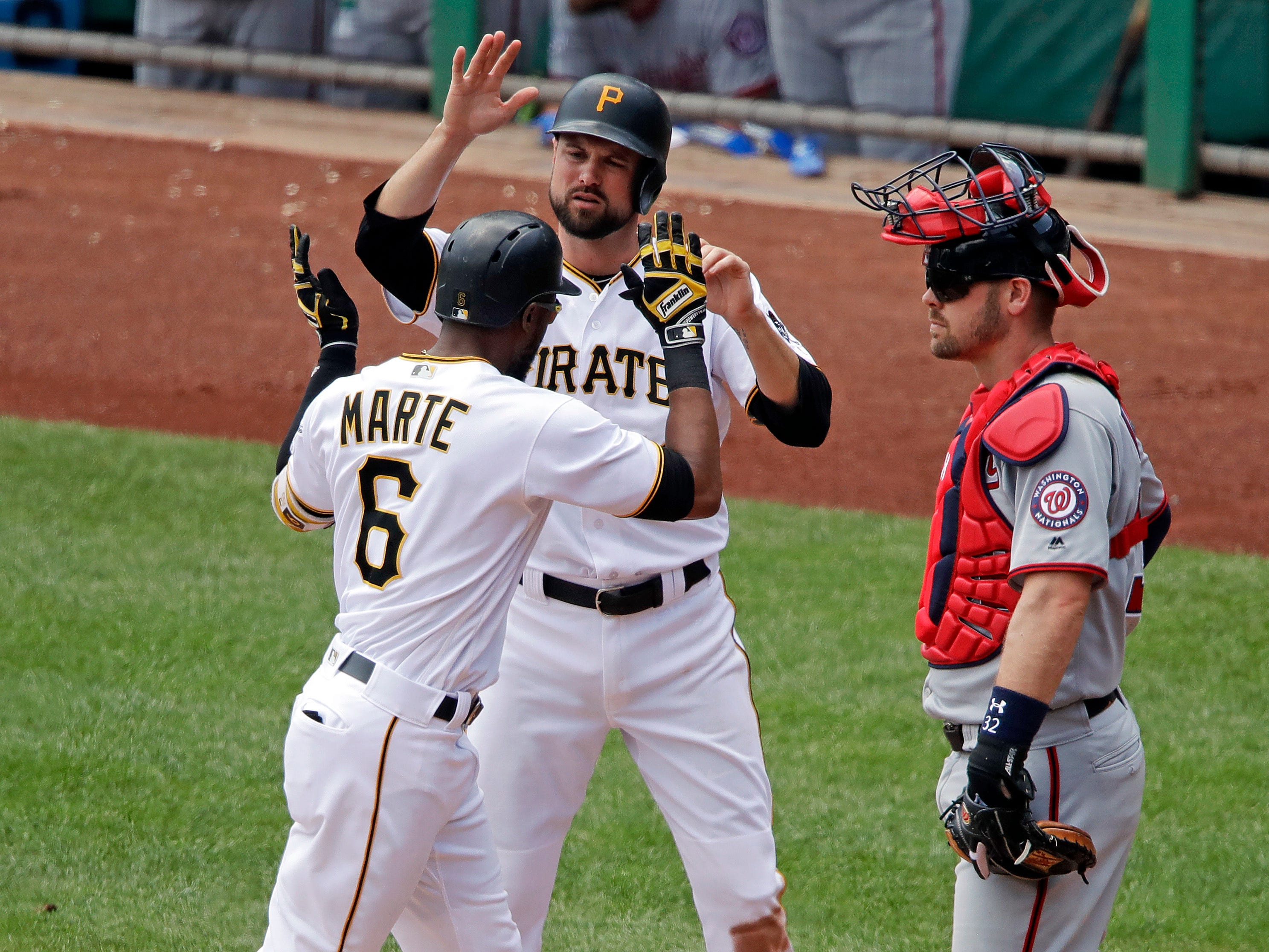 Washington Nationals catcher Matt Wieters, left, waits as Pittsburgh Pirates' Starling Marte celebrates with Jordy Mercer after hitting a two-run home run off Nationals starting pitcher Gio Gonzalez in the third inning of a game in Pittsburgh, Wednesday, July 11, 2018.