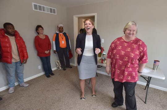 Homeowner Maria Walkenbach, right, blushes as Bridging Neighborhoods Director Heather Zygmontowicz congratulates her during a media event in the living room of her newly renovated home in Detroit's Warrendale  neighborhood. She traded in her deed on her previous home in Delray to make way for the Gordie Howe international bridge.