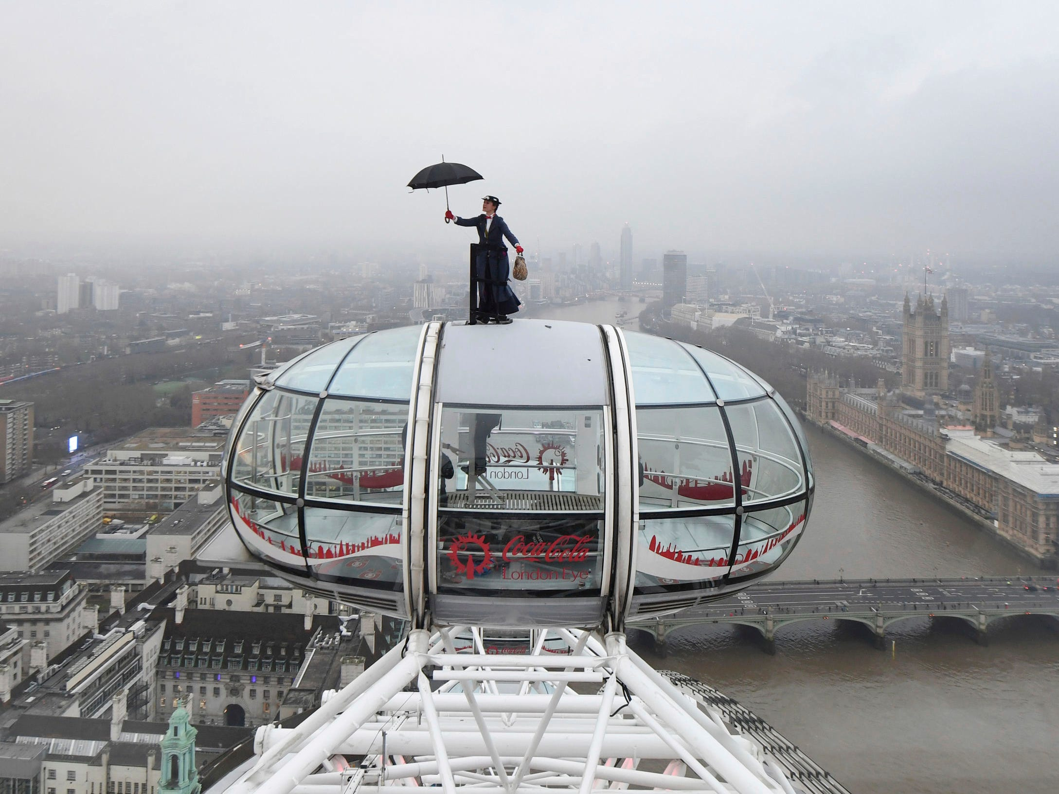 """Ahead of the European movie premiere of """"Mary Poppins Returns,"""" a stunt double rides atop the London Eye in central London with the Houses of Parliament on the banks of the River Thames, right, Wednesday Dec. 12, 2018."""