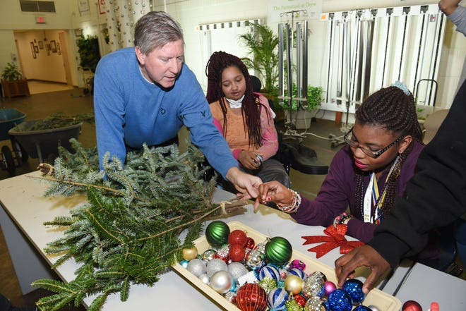 Drew Transition Center teacher Michael Craig, left, works with students Dreia Davis and Jazamine Veasley in making holiday door swag at the vocational horticulture program for cognitively impaired students.