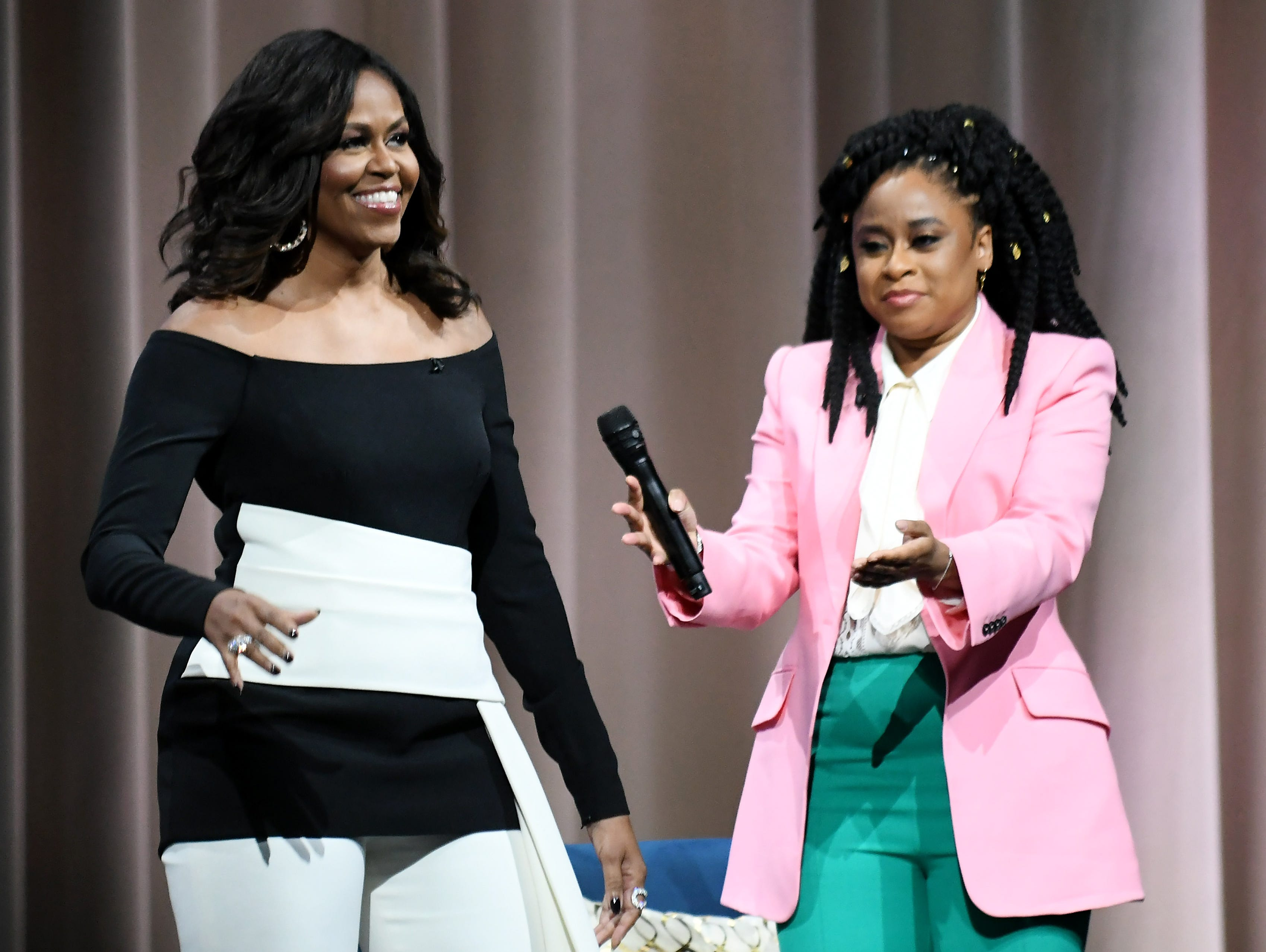 Michelle Obama comes on stage with moderator Phoebe Robinson, right, at Becoming: An Intimate Conversation with Michelle Obama at Little Caesars Arena in Detroit on Dec. 11, 2018.