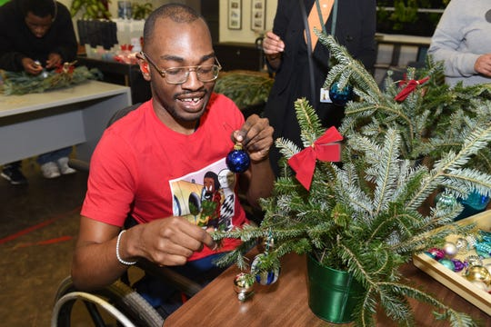 Drew Transition Center student Jaylan Yancy makes a holiday table centerpiece.