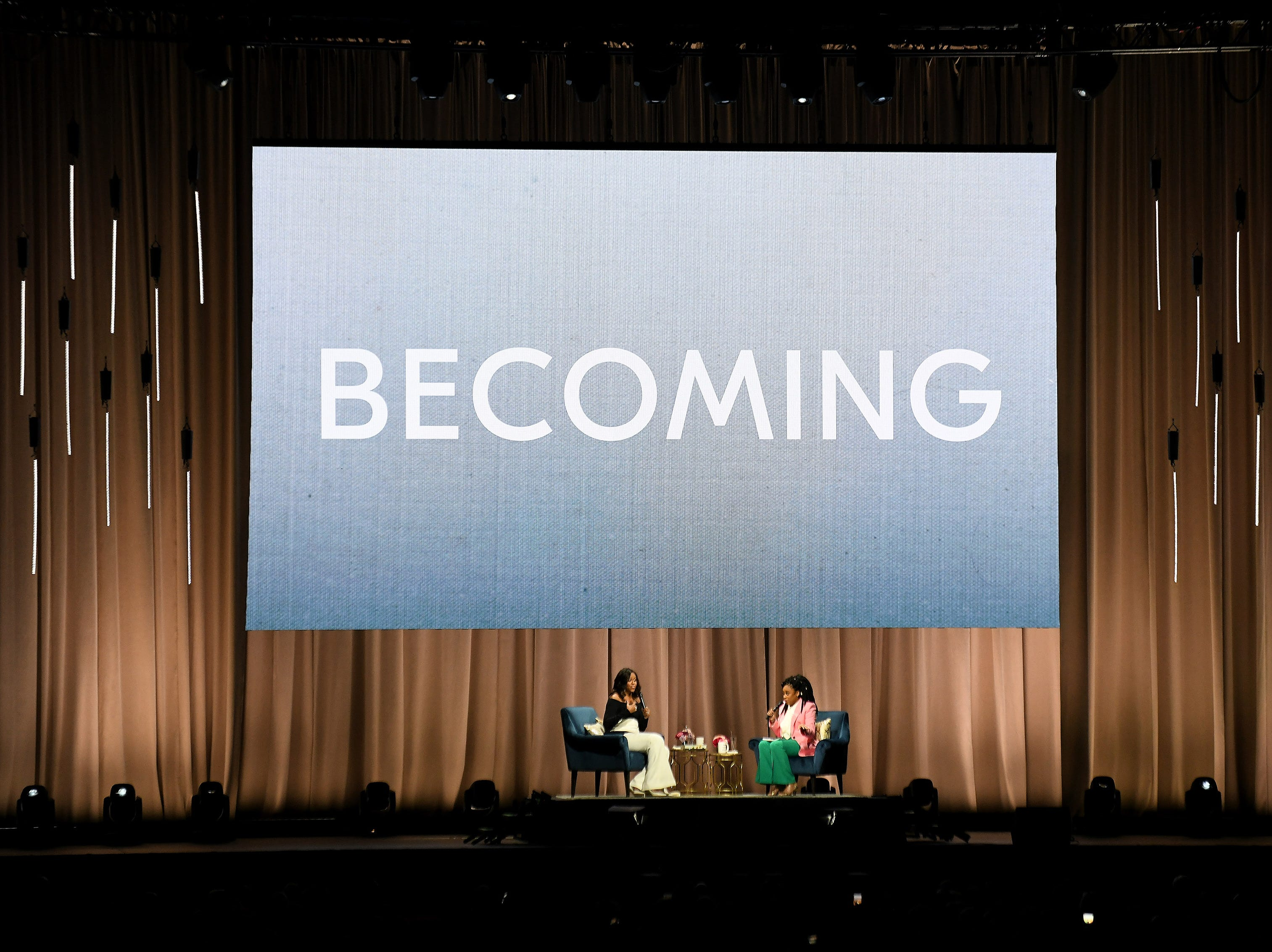 Michelle Obama on stage with moderator Phoebe Robinson, right, at Becoming: An Intimate Conversation with Michelle Obama at Little Caesars Arena in Detroit on Dec. 11, 2018.