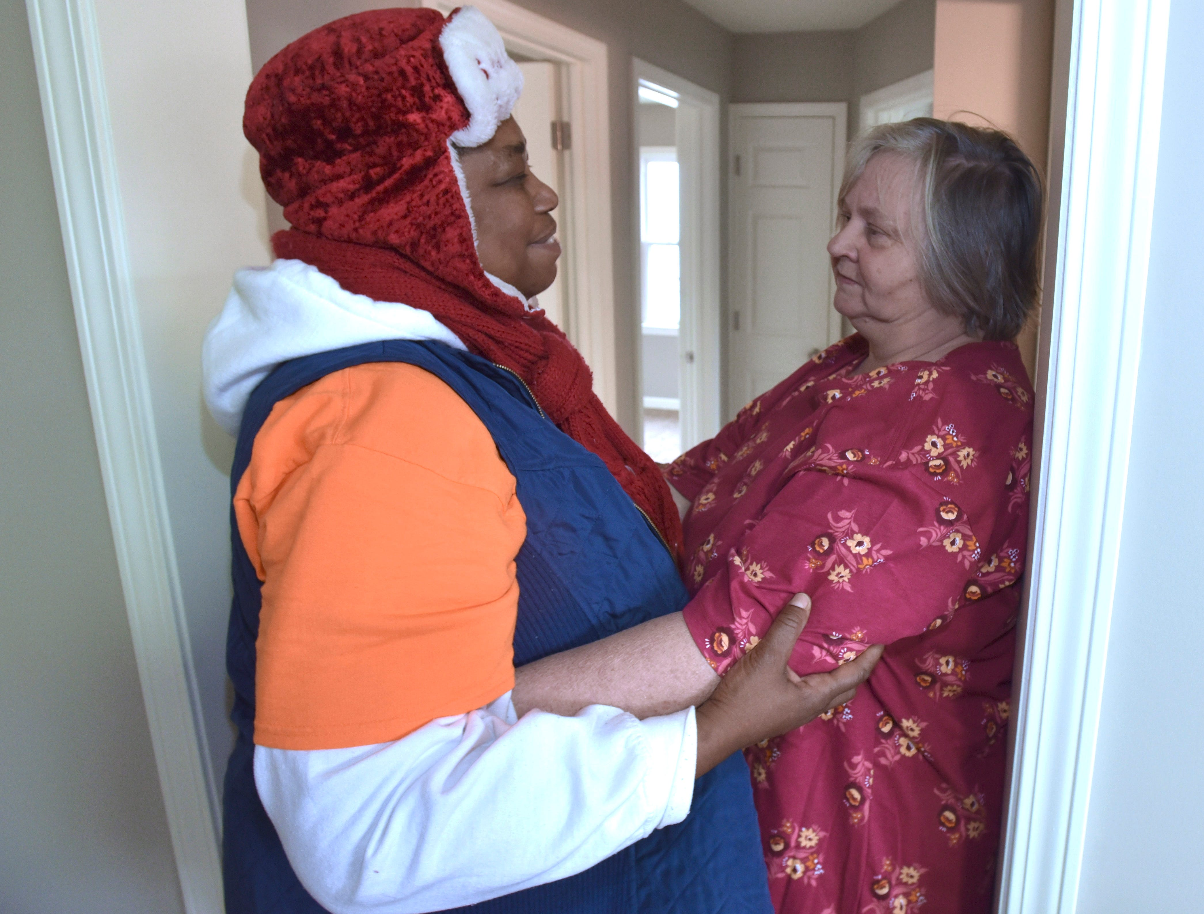 Homeowner Maria Walkenbach, right, gets a hug from Warrendale resident  and neighborhood leader Clois Foster.