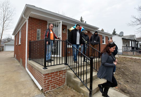 Attendees stand on the front porch.