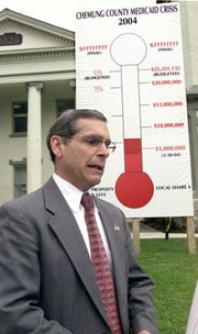Chemung County Executive Tom Santulli discusses the high cost of Medicaid during the 2004 unveiling of a new sign in front of the Chemung County Courthouse in Elmira.