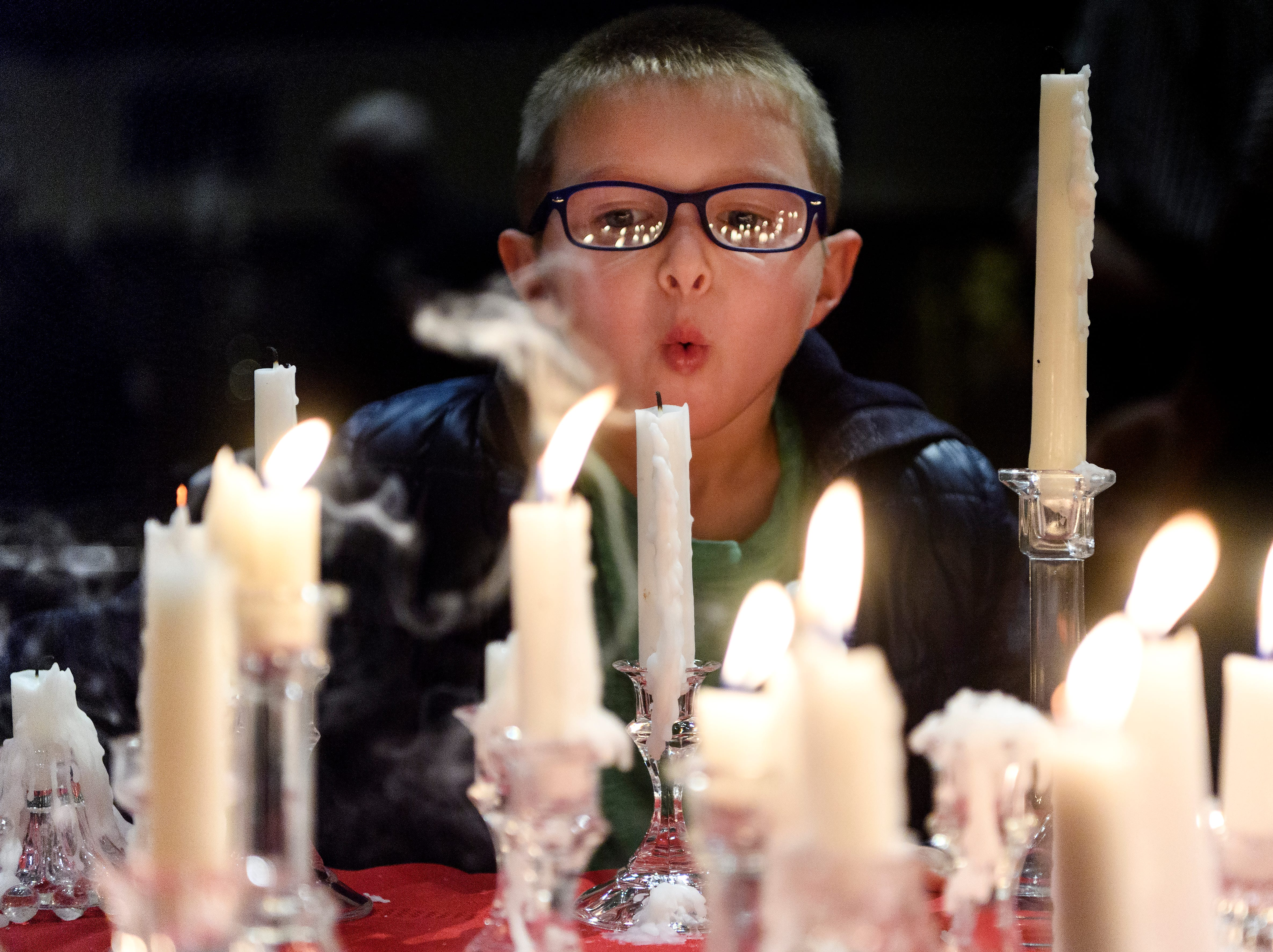 Kaleb Herron, 5, helps blow out candles at the end of the 18th annual Homeless Memorial service organized by Aurora, a local non-profit serving the homeless population, at Trinity United Methodist Church in Evansville, Ind., Tuesday, Dec. 11, 2018. Herron's uncle, Ronald Murray died in October and was memorialized by Herron's mother, Leann Herron, during the ceremony.