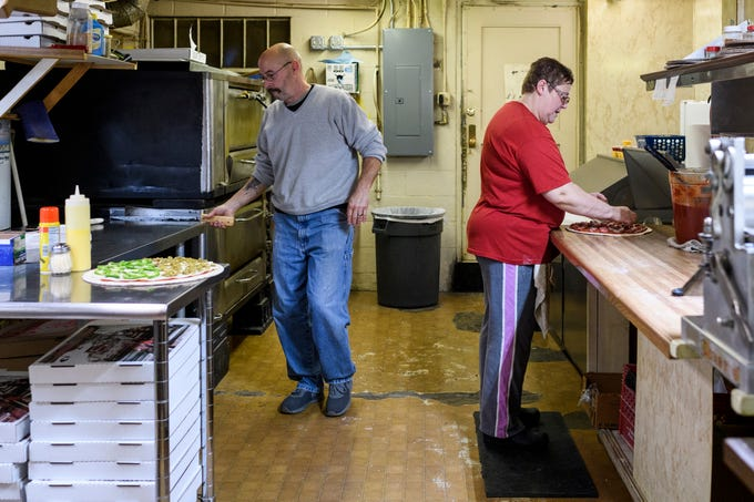 Greg, left, and Judy Roach, right, make pizzas at their restaurant, Stan's Una Pizza, located on Evansville's west side, Friday night, Dec. 7, 2018. The couple is retiring from the pizza business and will be shutting down the restaurant after Sunday, Dec. 30.