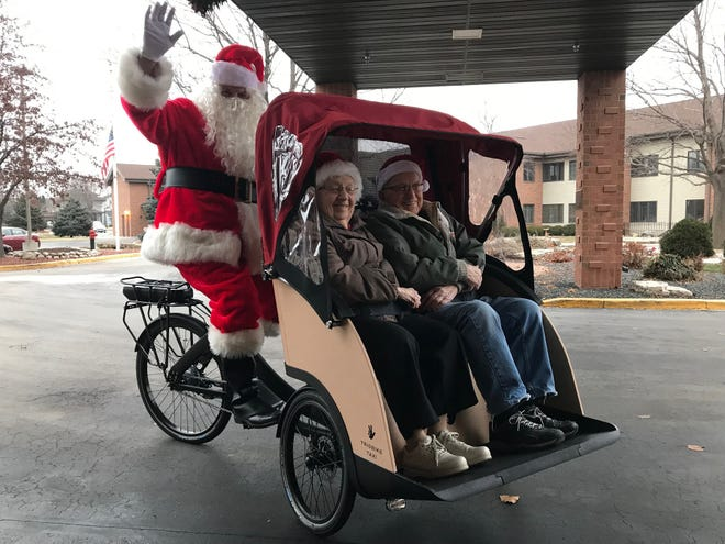Santa (Dave Gitter) spends some quality time with Elmer and Julitta Schmitz, St. Francis Home assisted living residents. St. Francis recently acquired two new trishaw bicycles, thanks to funds from the Agnesian HealthCare Foundation and a state grant.