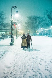 Strollers in period costumes walk along a snowy sidewalk during Holiday Nights at Greenfield Village.