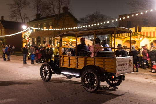 Guests can be driven in a Model T Ford through the streets of Greenfield Village during Holiday Nights.