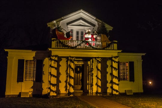 Santa greets guests from the balcony of the Robert Frost House during Holiday Nights.