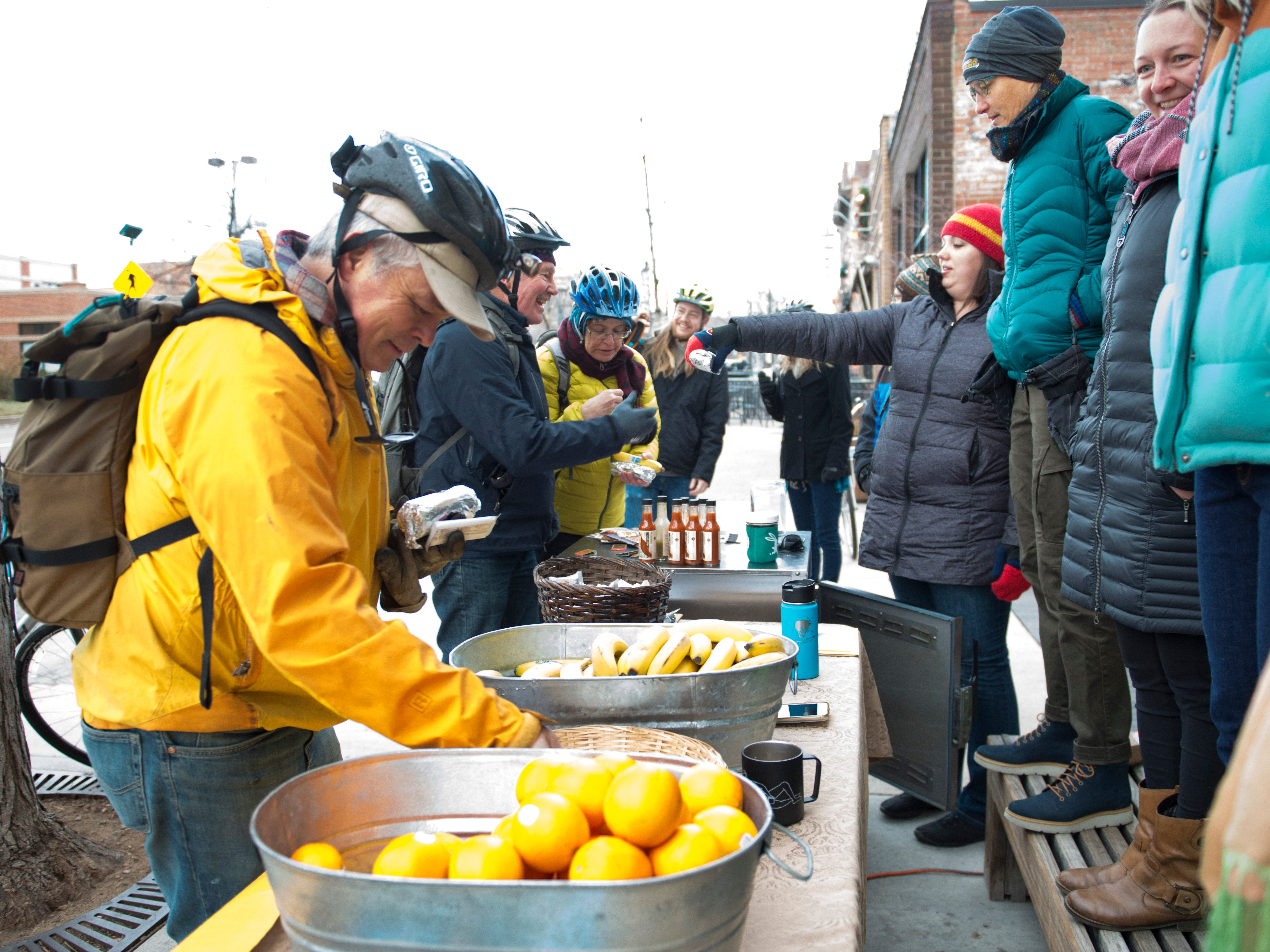 People line up for breakfast outside of the Mountain Avenue Market during Winter Bike to Work Day on Wednesday, December 12, 2018. Commuters were treated to free breakfast and coffee at nearly 50 stations around Fort Collins.